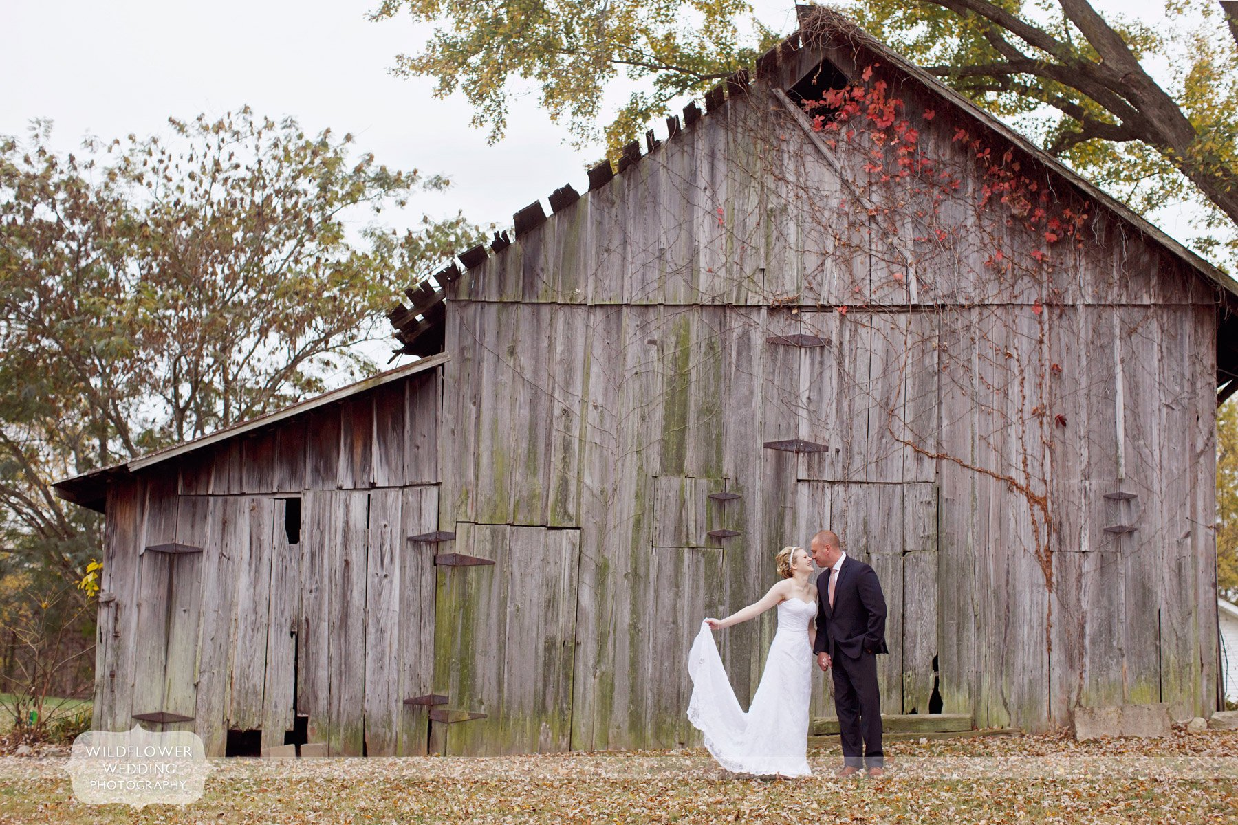 bride and groom stand outside of an old barn in rocheport, mo for their fall wedding