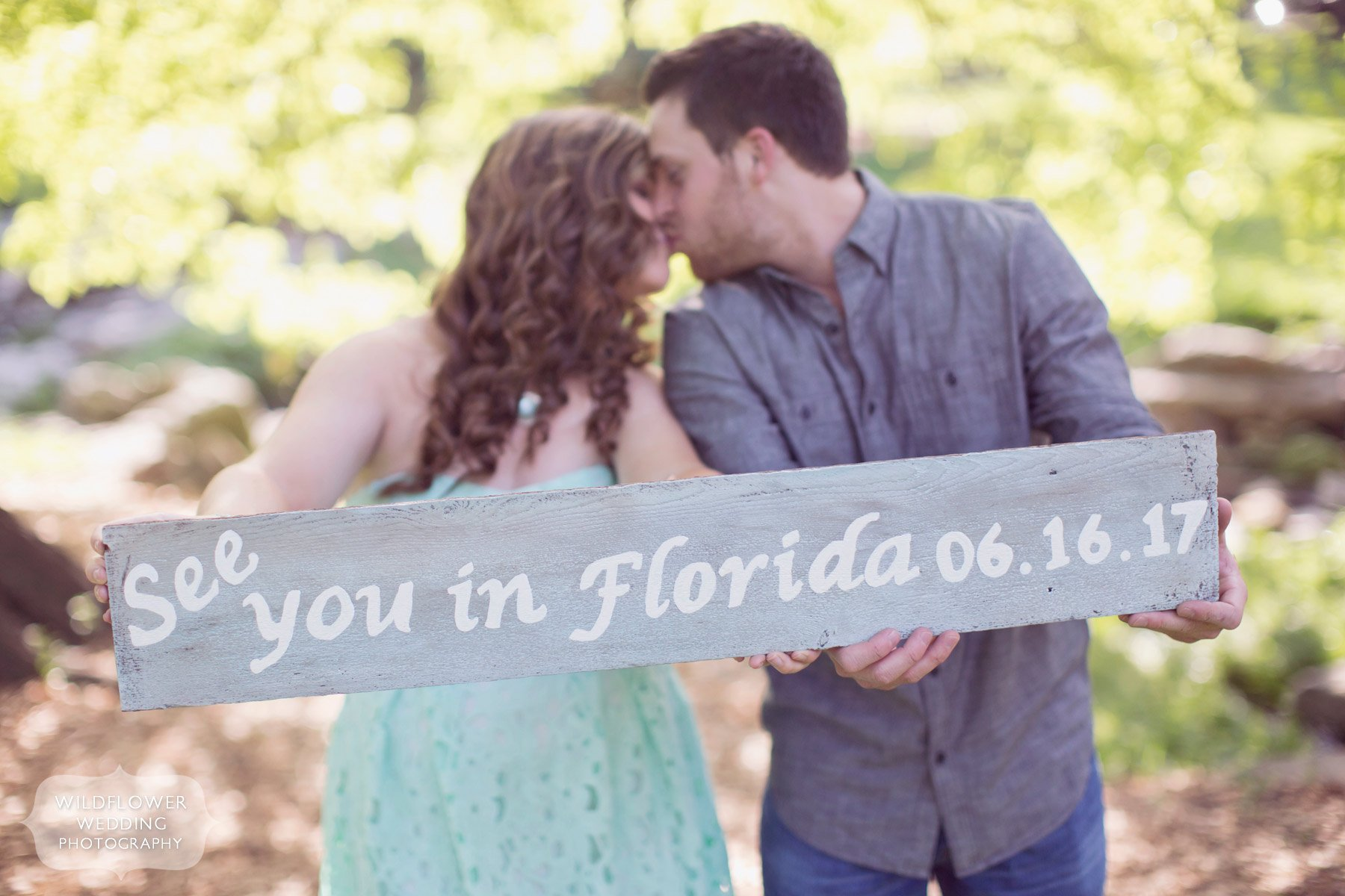 Spring engagement photography session at Peace Park in Columbia, MO. This couple is holding a rustic wood sign for their save the date card!