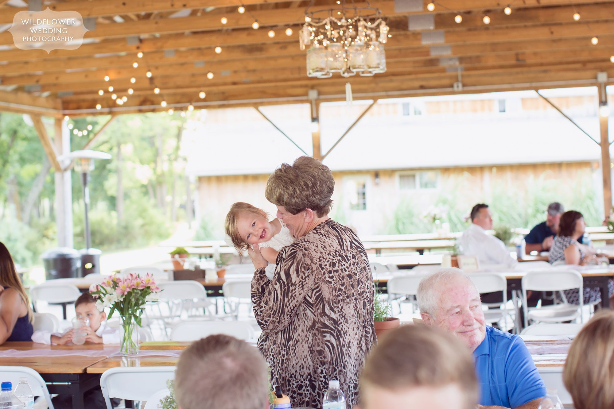 Great documentary wedding photo of the grandmother smiling with her granddaughter after dinner in the covered pavilion at this country wedding venue.