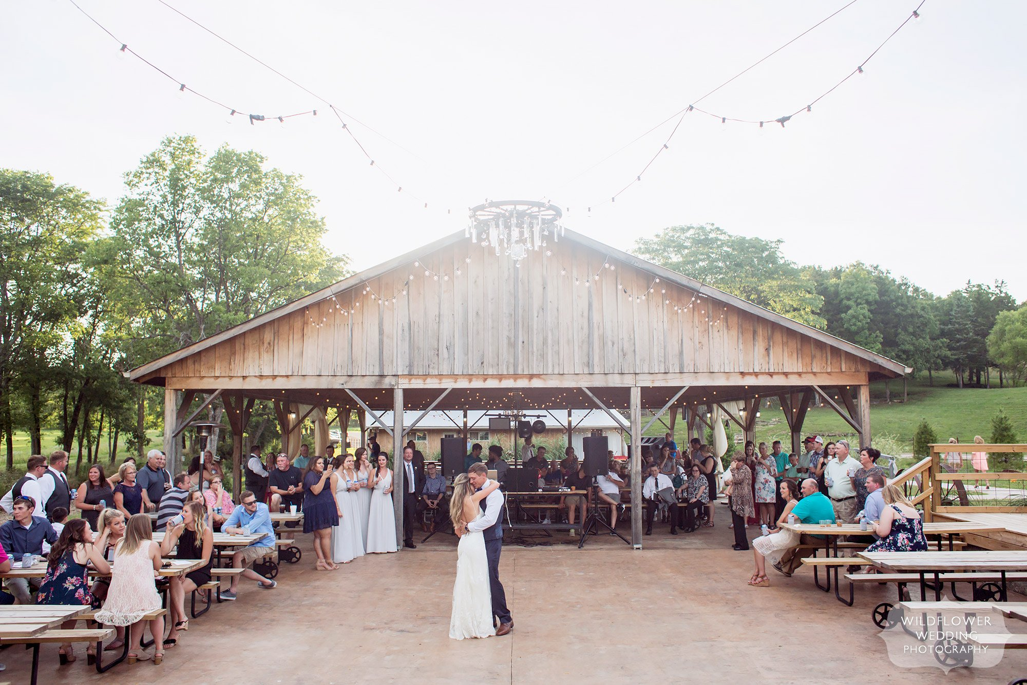 The bride and groom have their first dance outside under a canopy of twinkle lights at this barn wedding venue in Westphalia, MO.