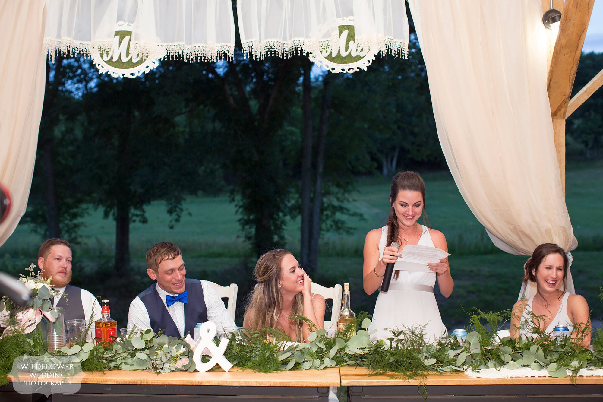 The maid of honor gives a speech while the bride and groom laugh under the covered pavilion for dinner.
