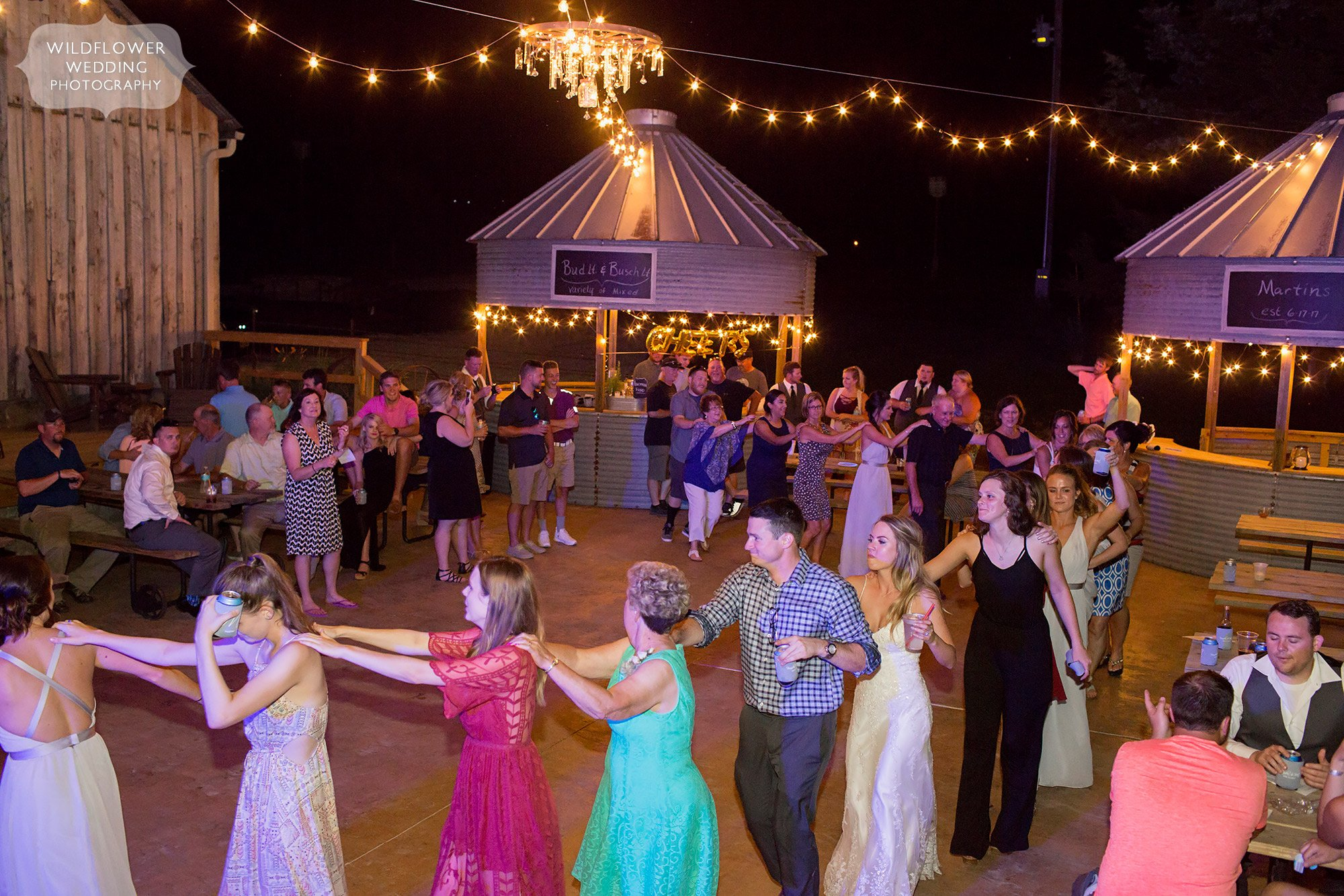 Wedding guests form a conga line on the outdoor dance patio at this barn venue in MO.