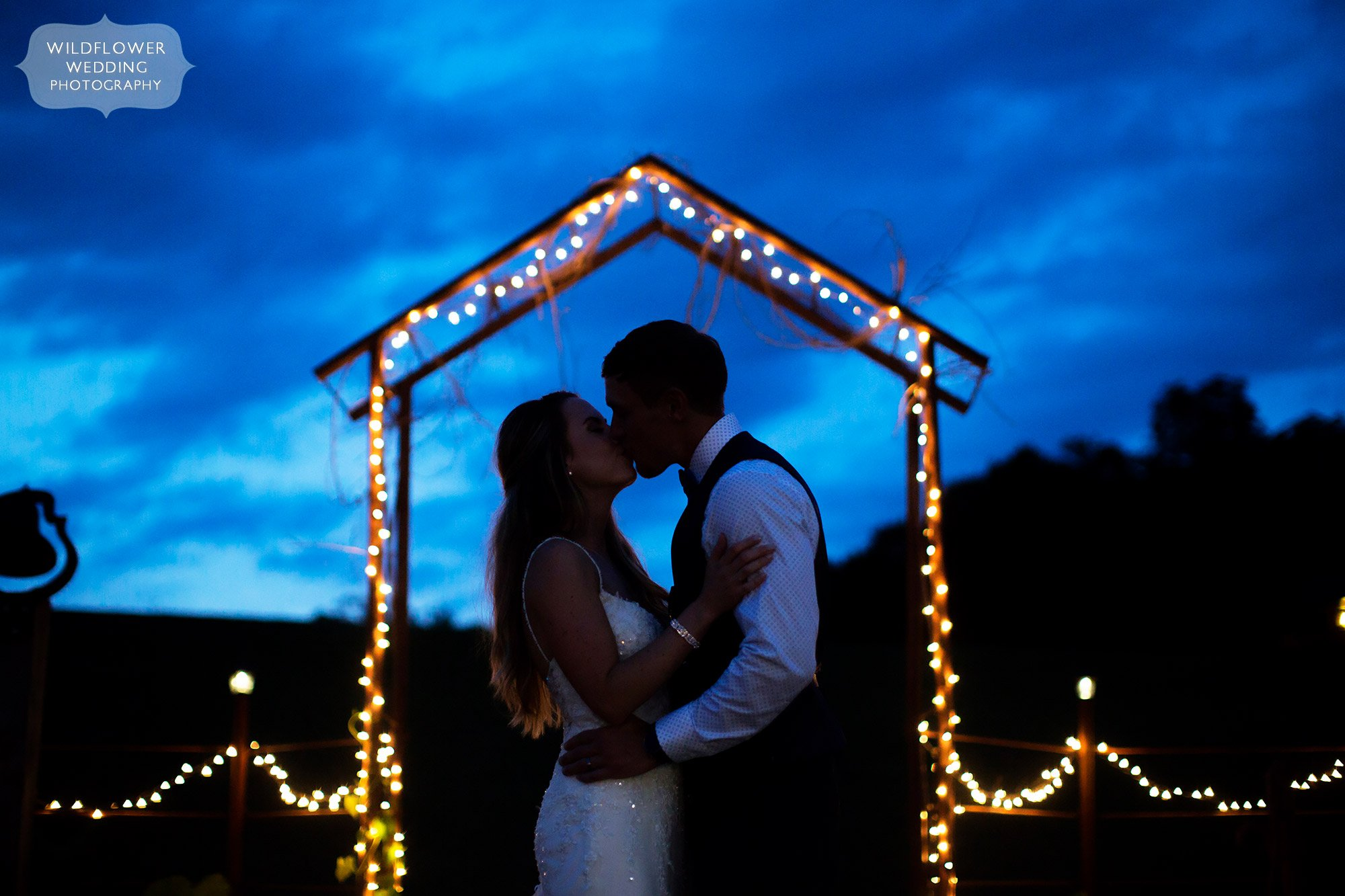 Bride and groom kiss under a twinkle light arch during twilight blue light sky in southern MO.