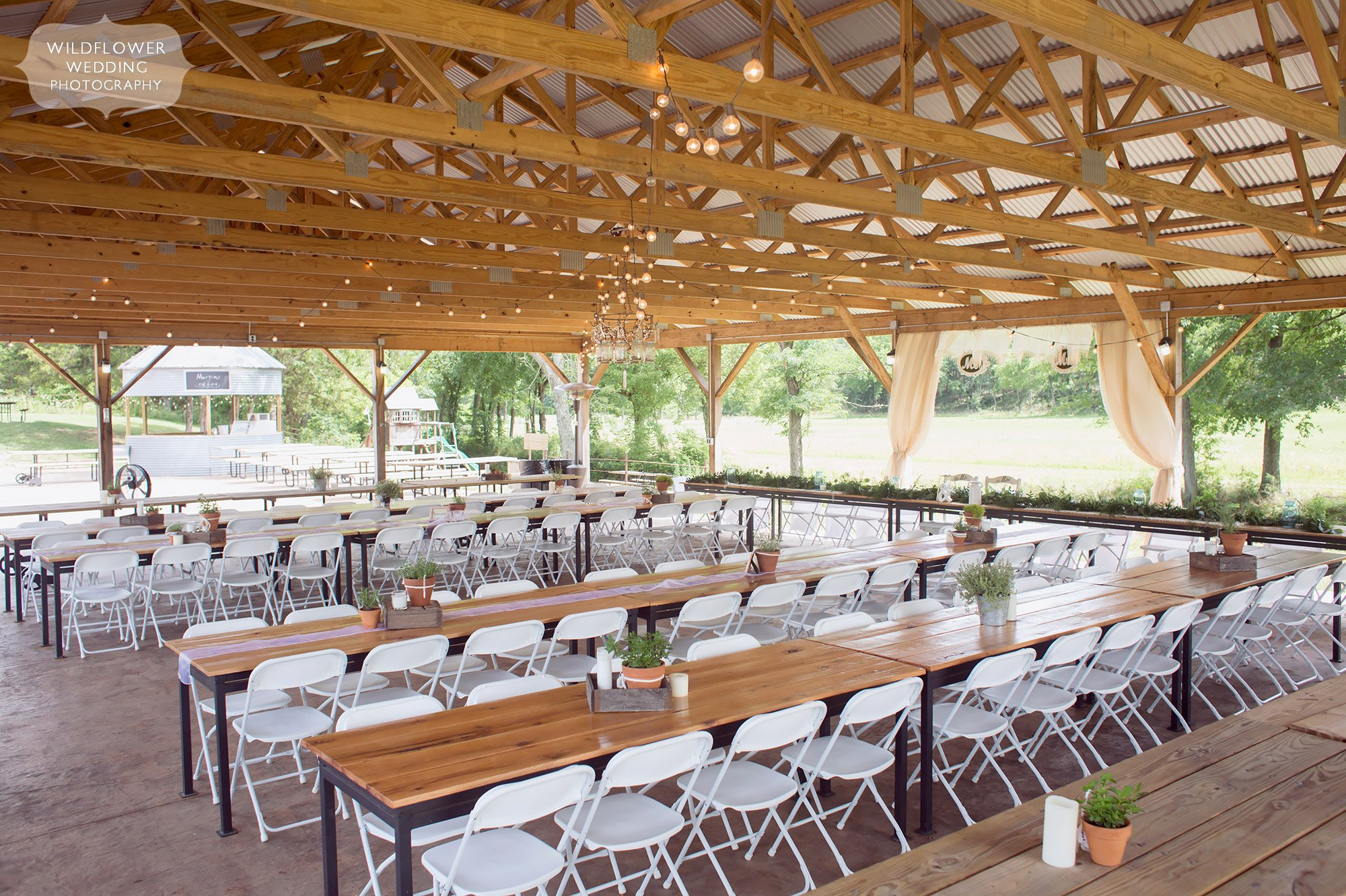 View of the dinner tables set up in the covered pavilion at this barn wedding venue at Kempker's Back 40 in southern MO.
