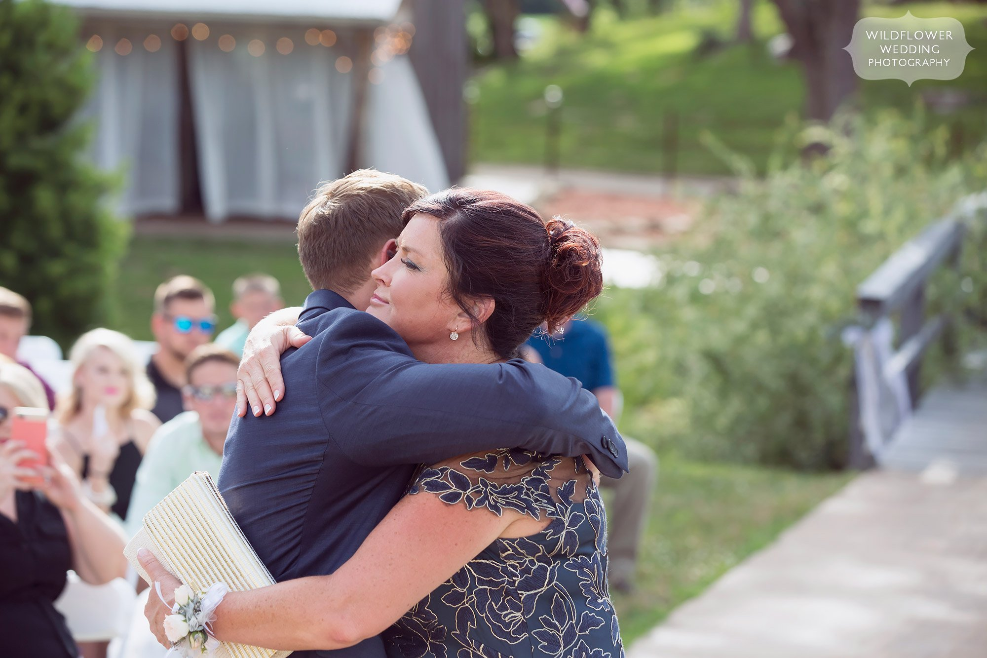 Candid photo of the groom hugging his mother in law before the outdoor ceremony at this barn wedding in southern MO.