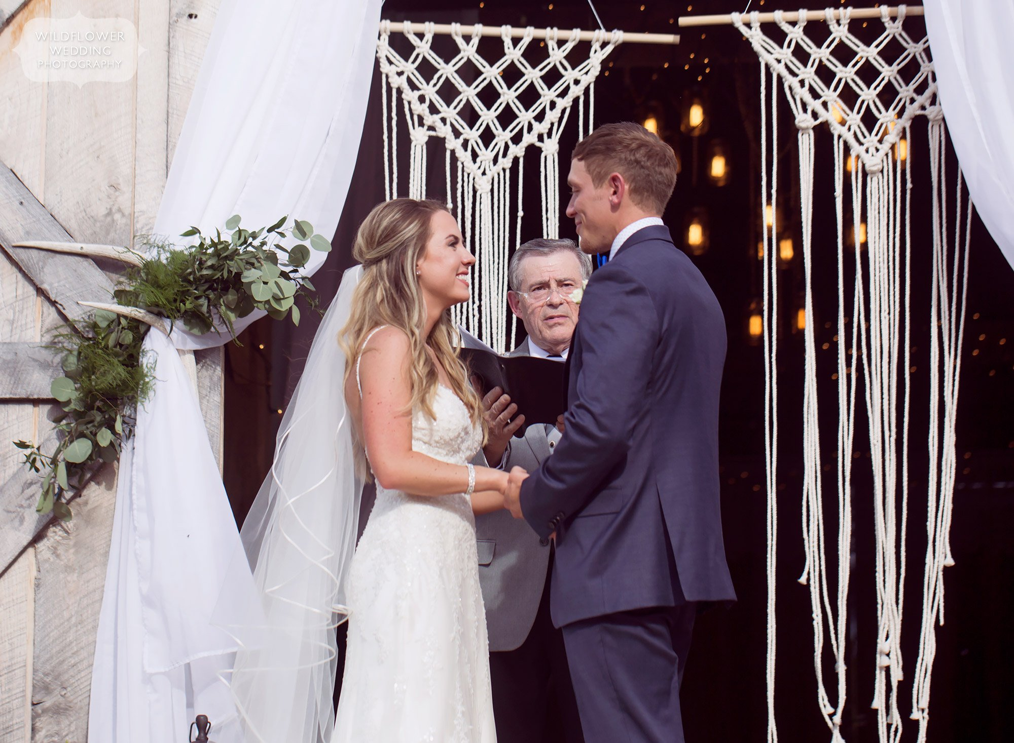 The bride and groom exchange vows in front of this white woven macrame backdrop in the barn doorway at Kempker's Back 40.