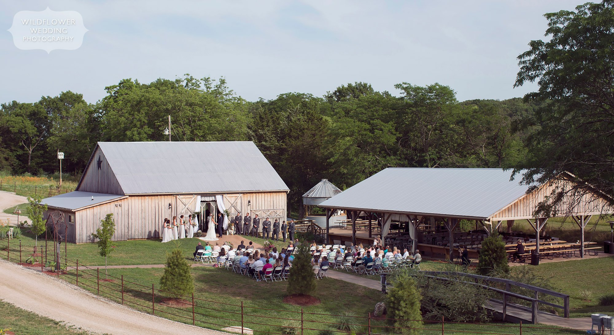 View of the outdoor ceremony in front of the reception barn at Kempker's Back 40, a rustic wedding venue in Westphalia.