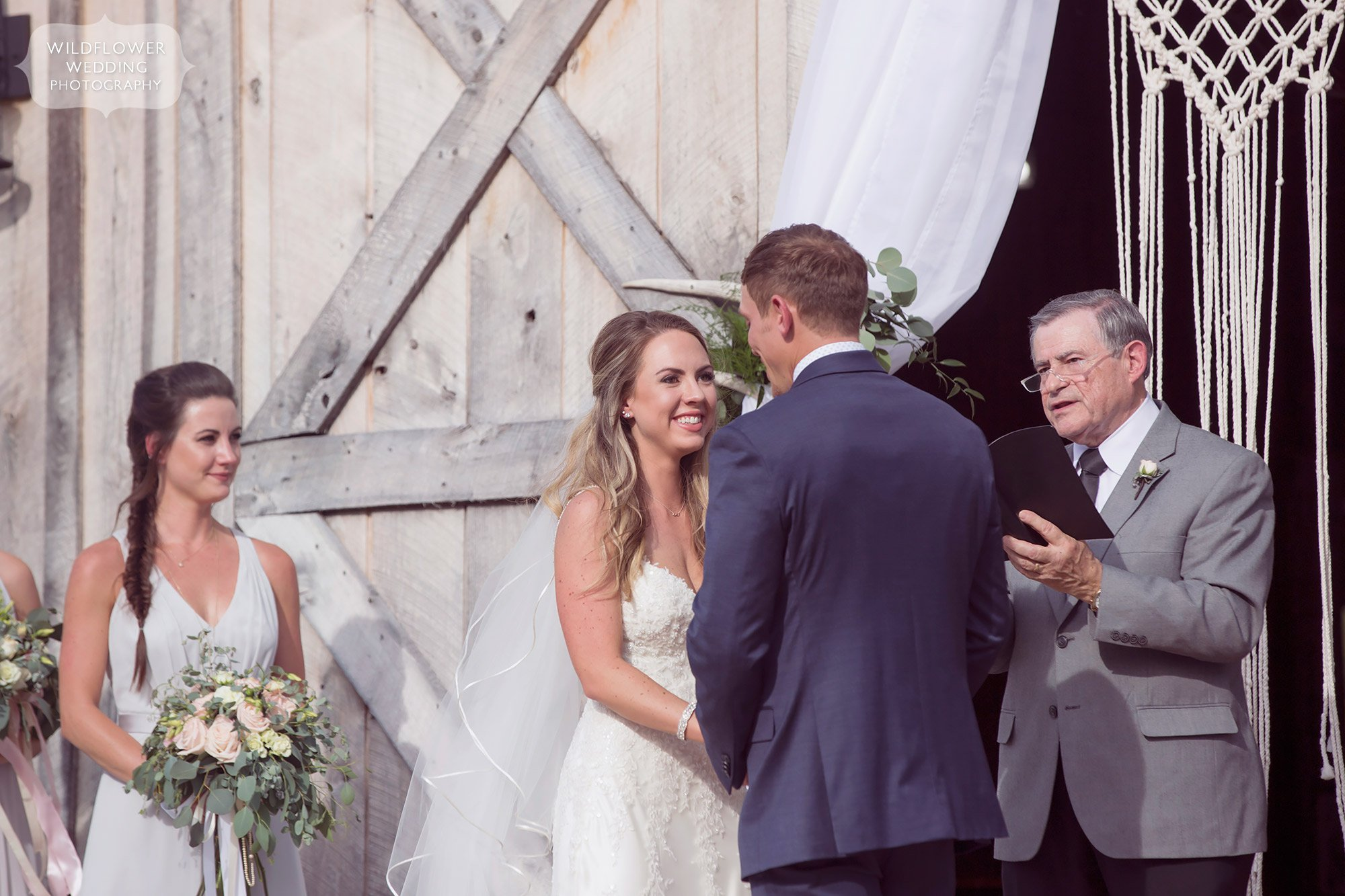 The happy bride looks at her groom during this natural wedding photo of the outdoor ceremony.