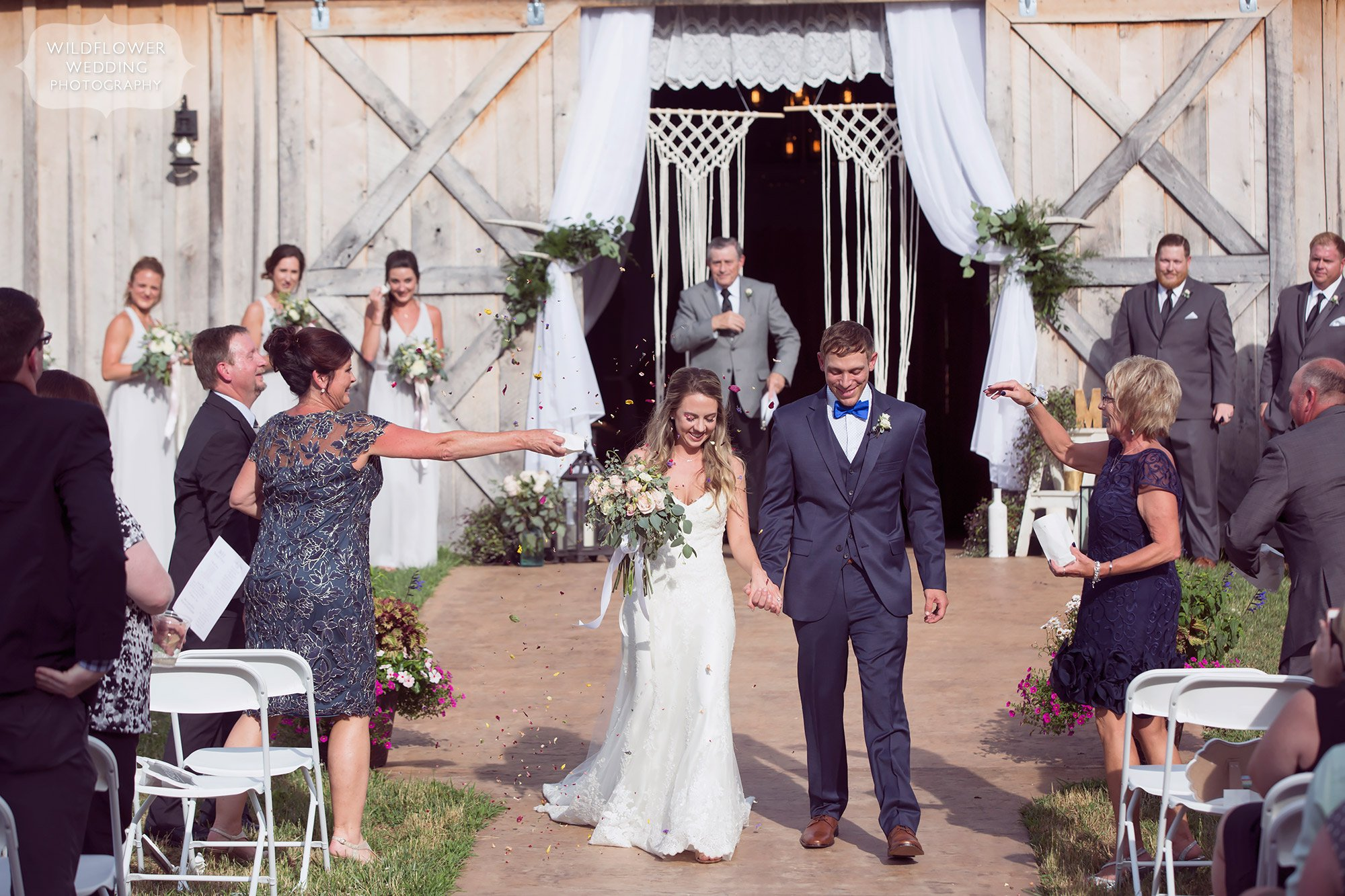The bride and groom have a colorful wedding ceremony exit walk as the guests throw dried wildflower petals at them at this barn wedding.