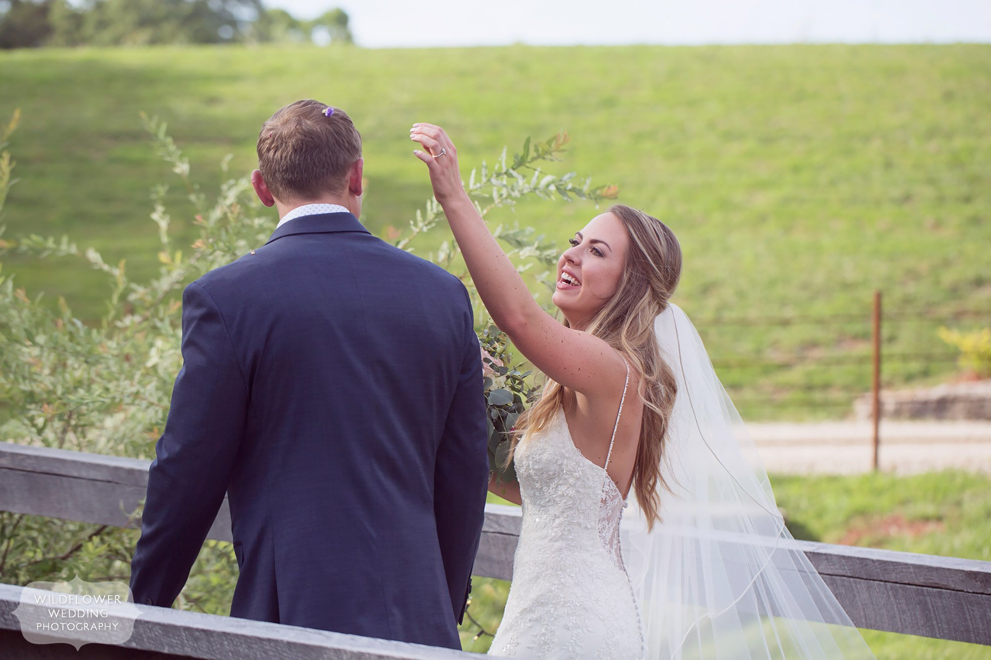 Candid wedding photography of the bride picking wildflowers out of the groom's hair after their outdoor ceremony in the country of southern MO.