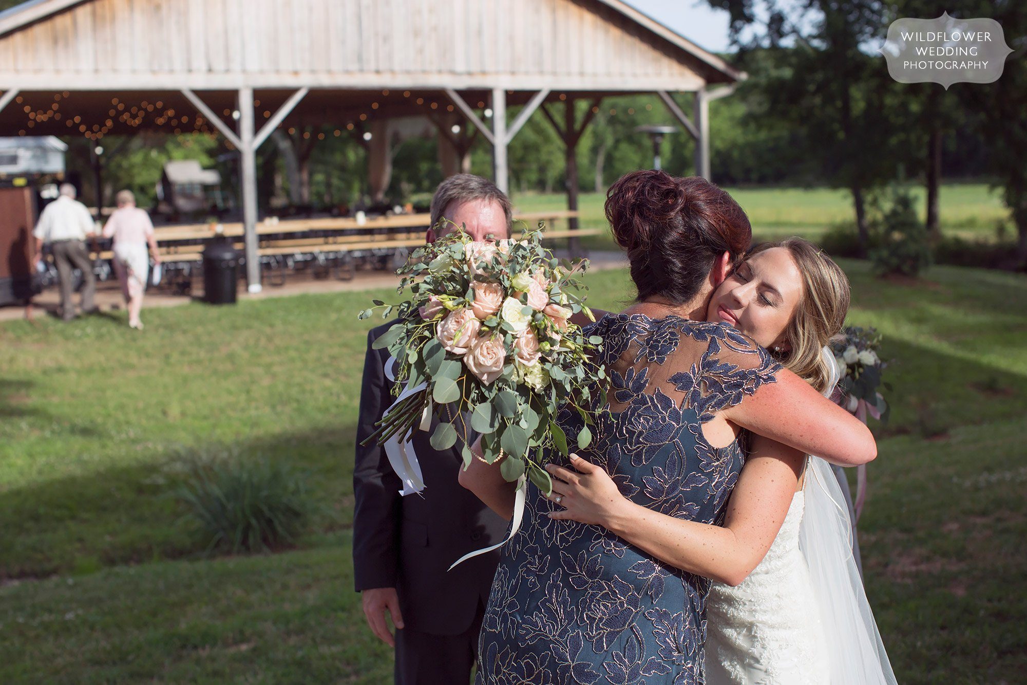 Emotional photo of the bride and her mom hugging after the barn ceremony.