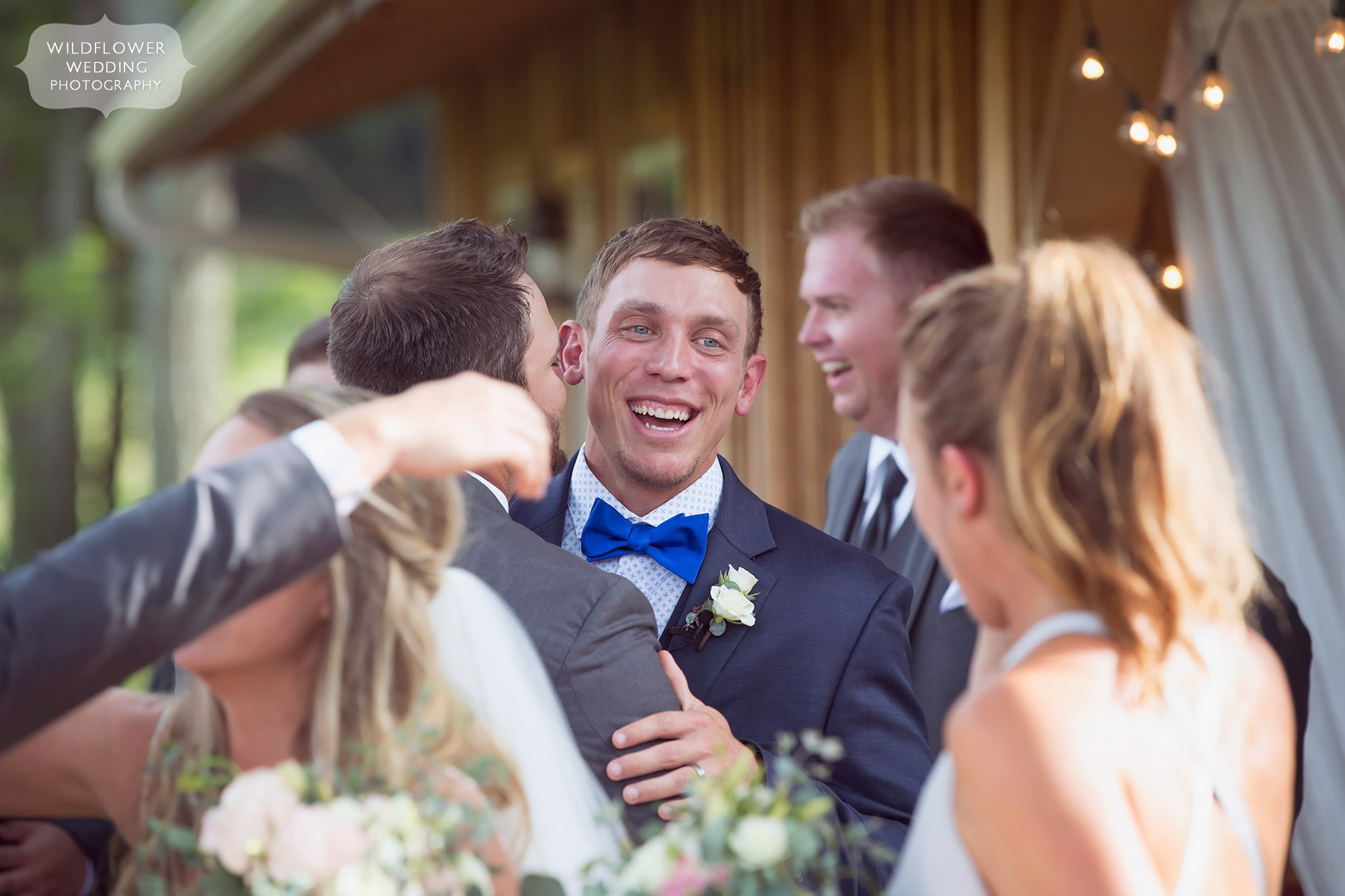 Love this bright and colorful photo of the groom smiling as friends hug him after the barn ceremony in southern MO.