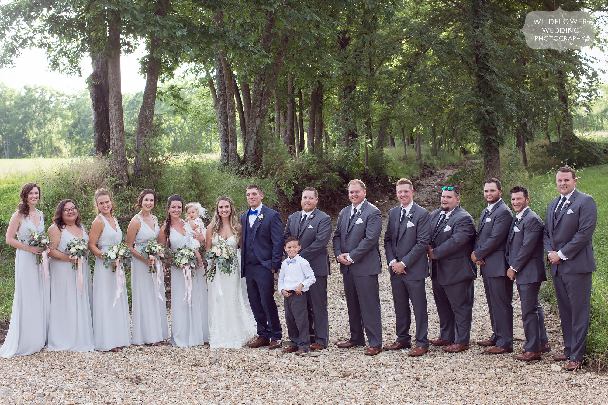 Wedding party poses in the rocky creekbed at this rustic barn wedding venue in Westphalia.