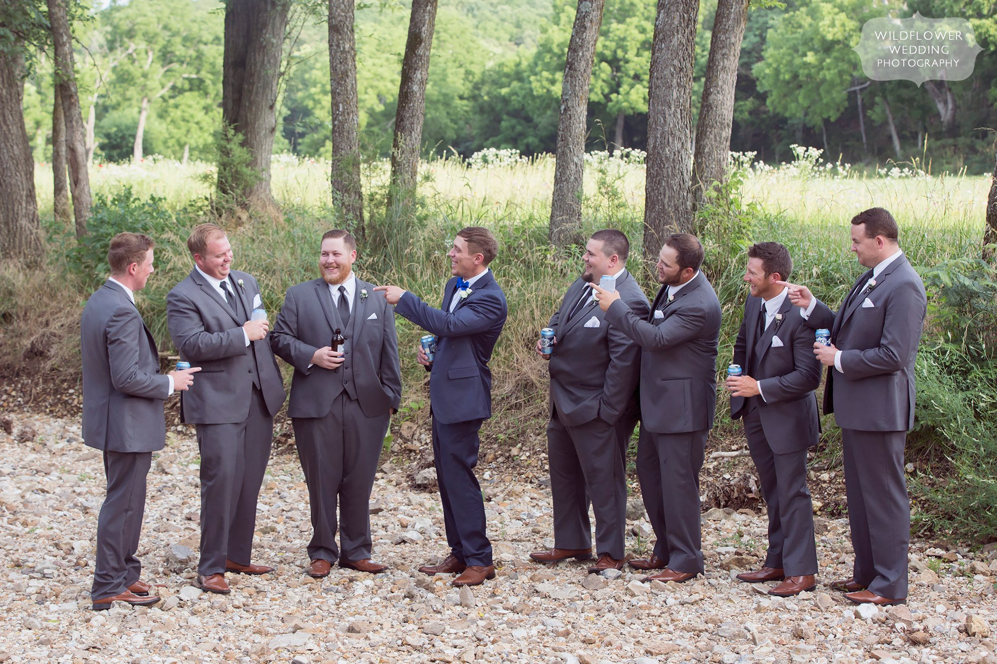 Funny photo of the groomsmen in the creek at this country wedding in MO.