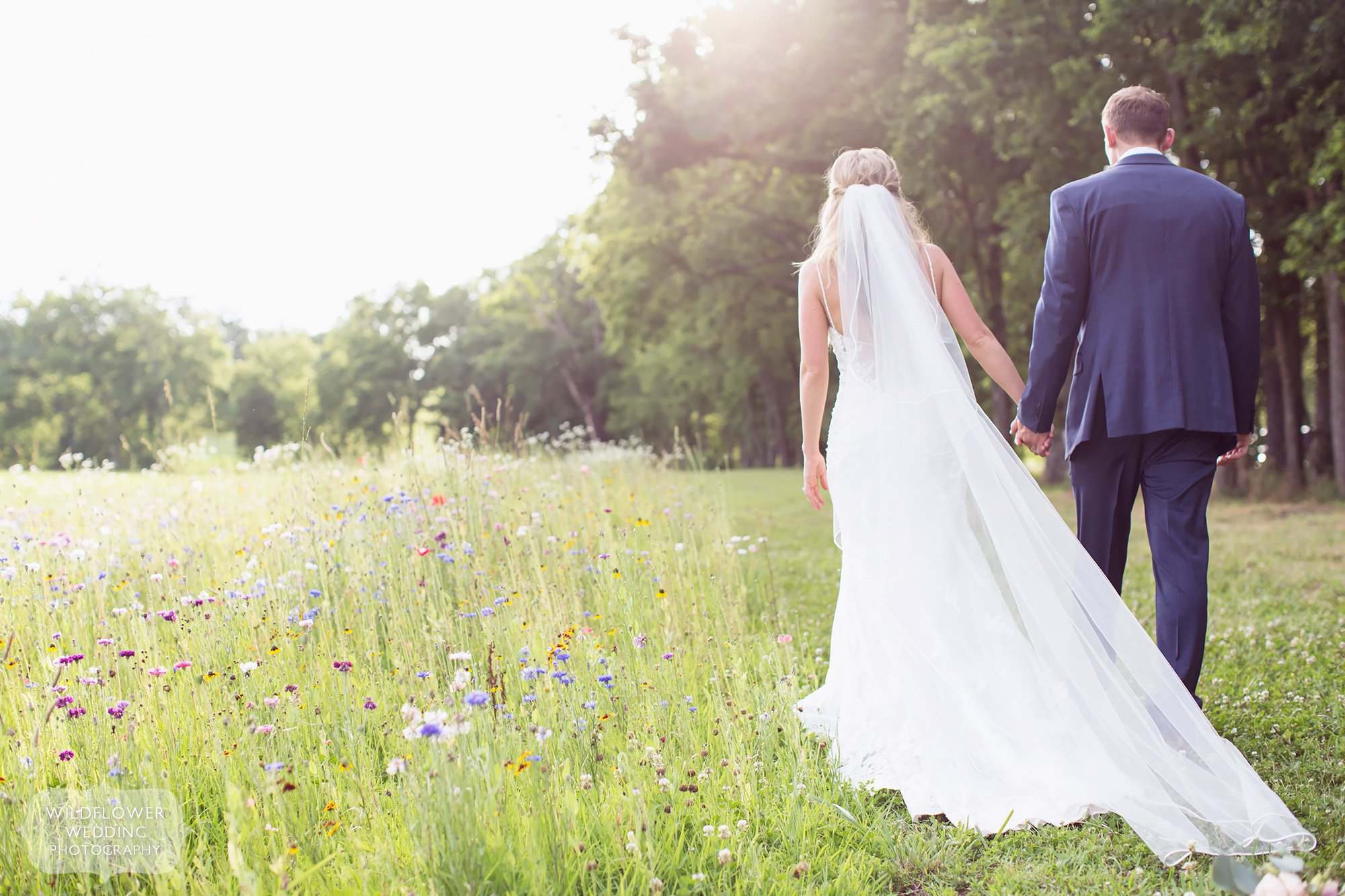 Romantic ethereal wedding photo of the bride and groom walking through a field of wildflowers at Kempker's Back 40 barn wedding venue.