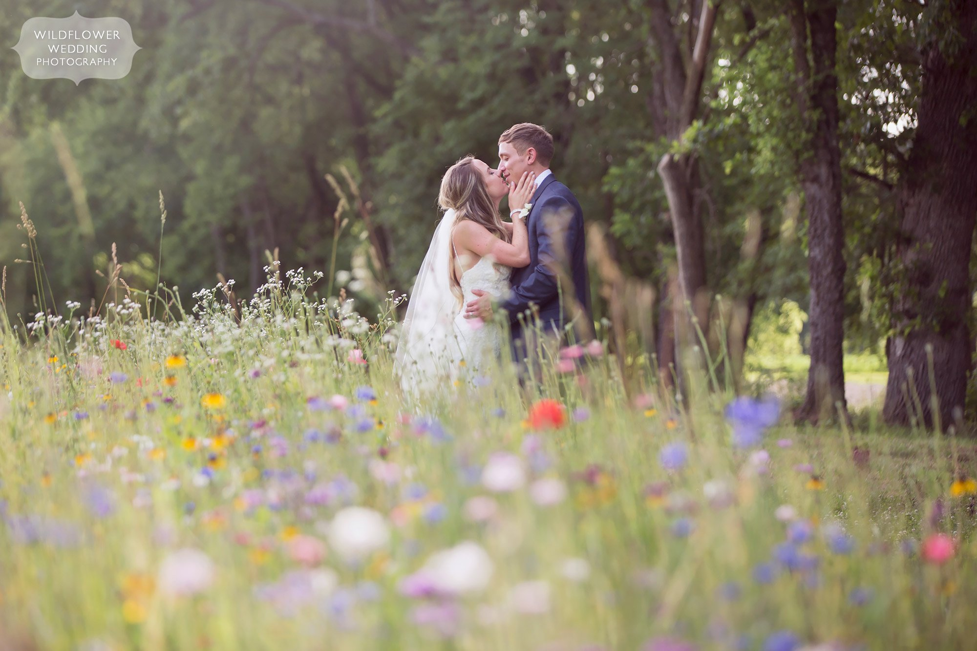 The bride and groom in a sexy kiss at this country wedding in a field of flowers at their Kempker's Back 40 barn wedding.