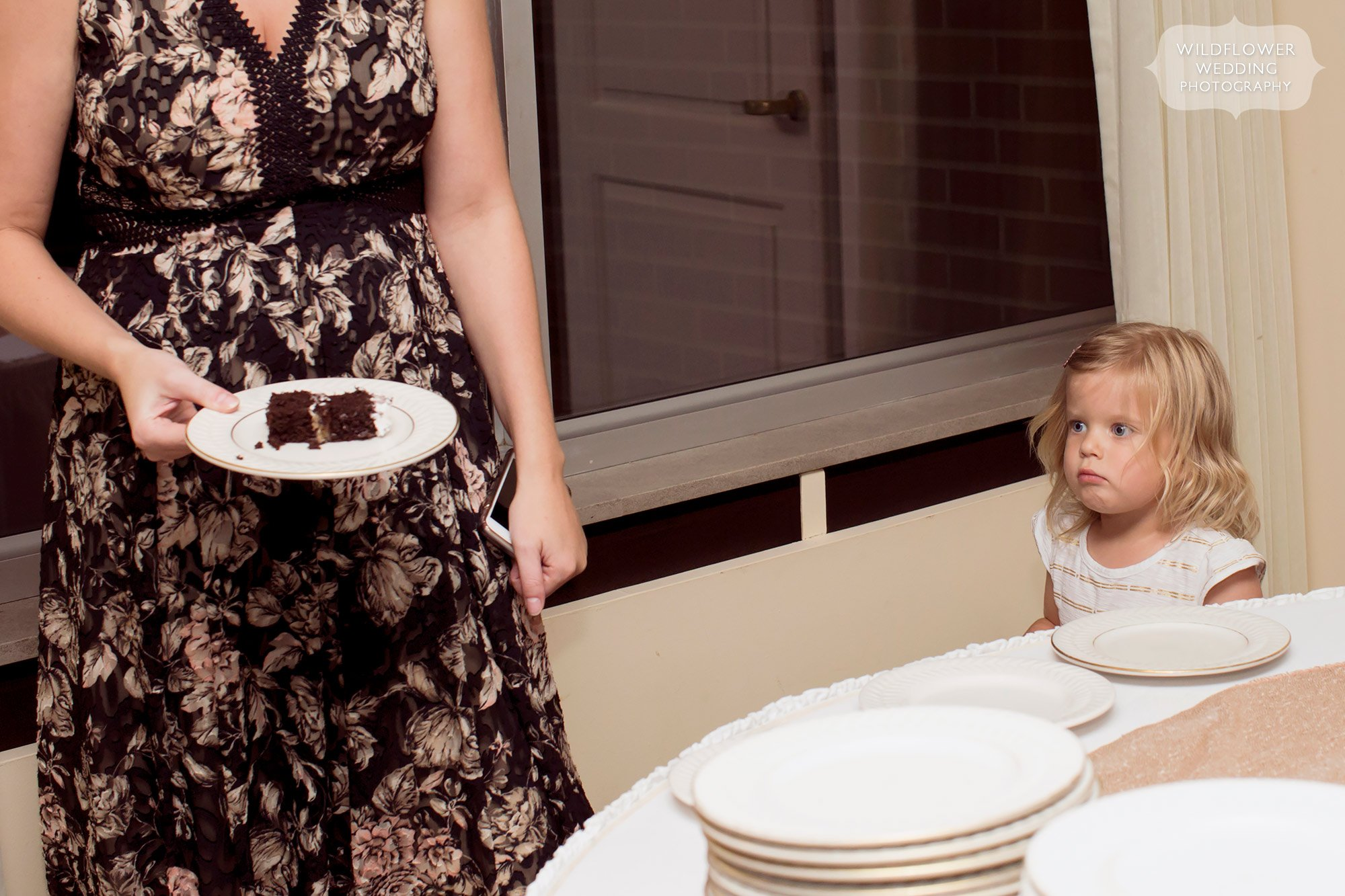 Funny documentary wedding photo of the flower girl looking at cake.