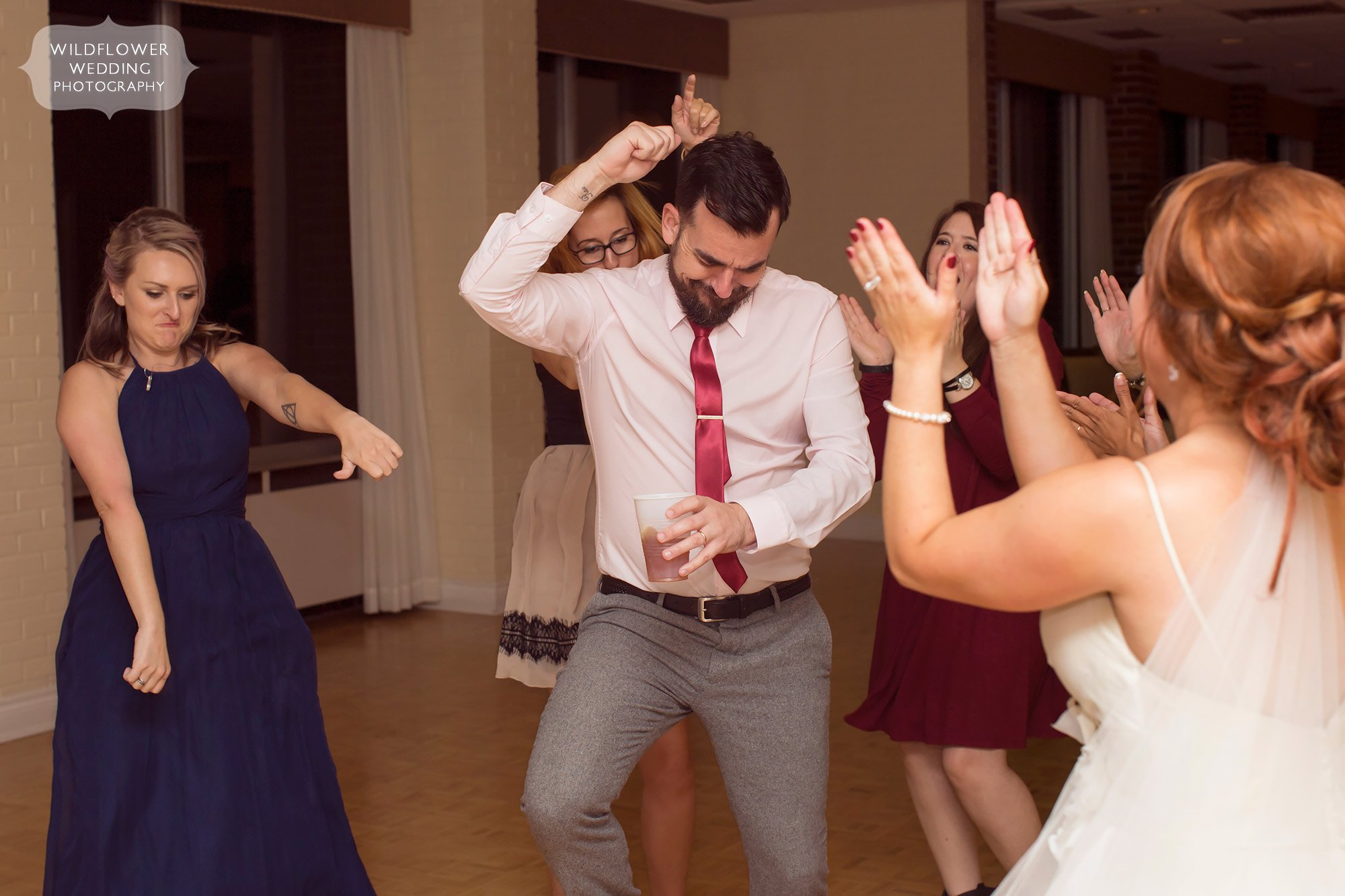 Funny friends during wedding reception dancing.