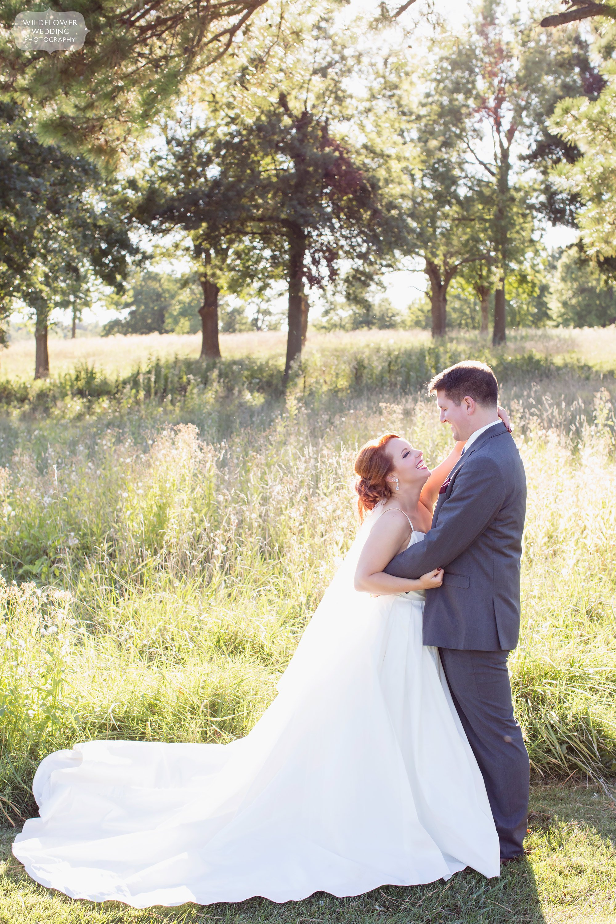 Bride and groom laughing in a field at their Jefferson City Country Club wedding in MO.