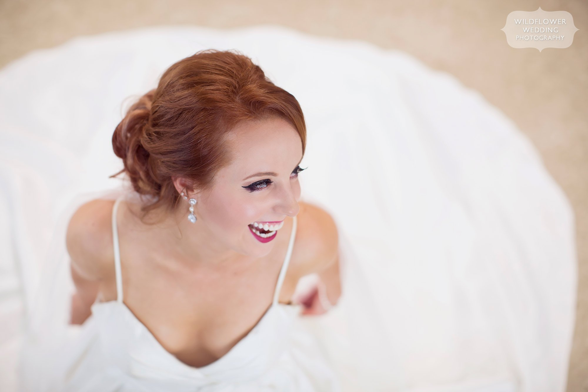 Beautiful portrait of bride laughing surrounded by dress at her Jefferson City, MO wedding.