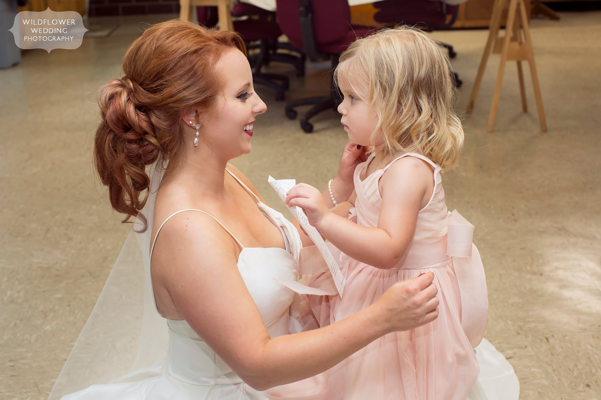 Bride holding hands with the flower girl at this Jeff City wedding.