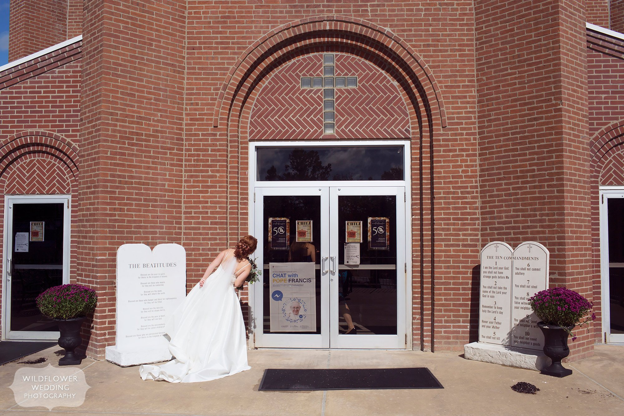 Great documentary wedding photo of the bride looking in the windows of the church before her Jeff City, MO wedding.