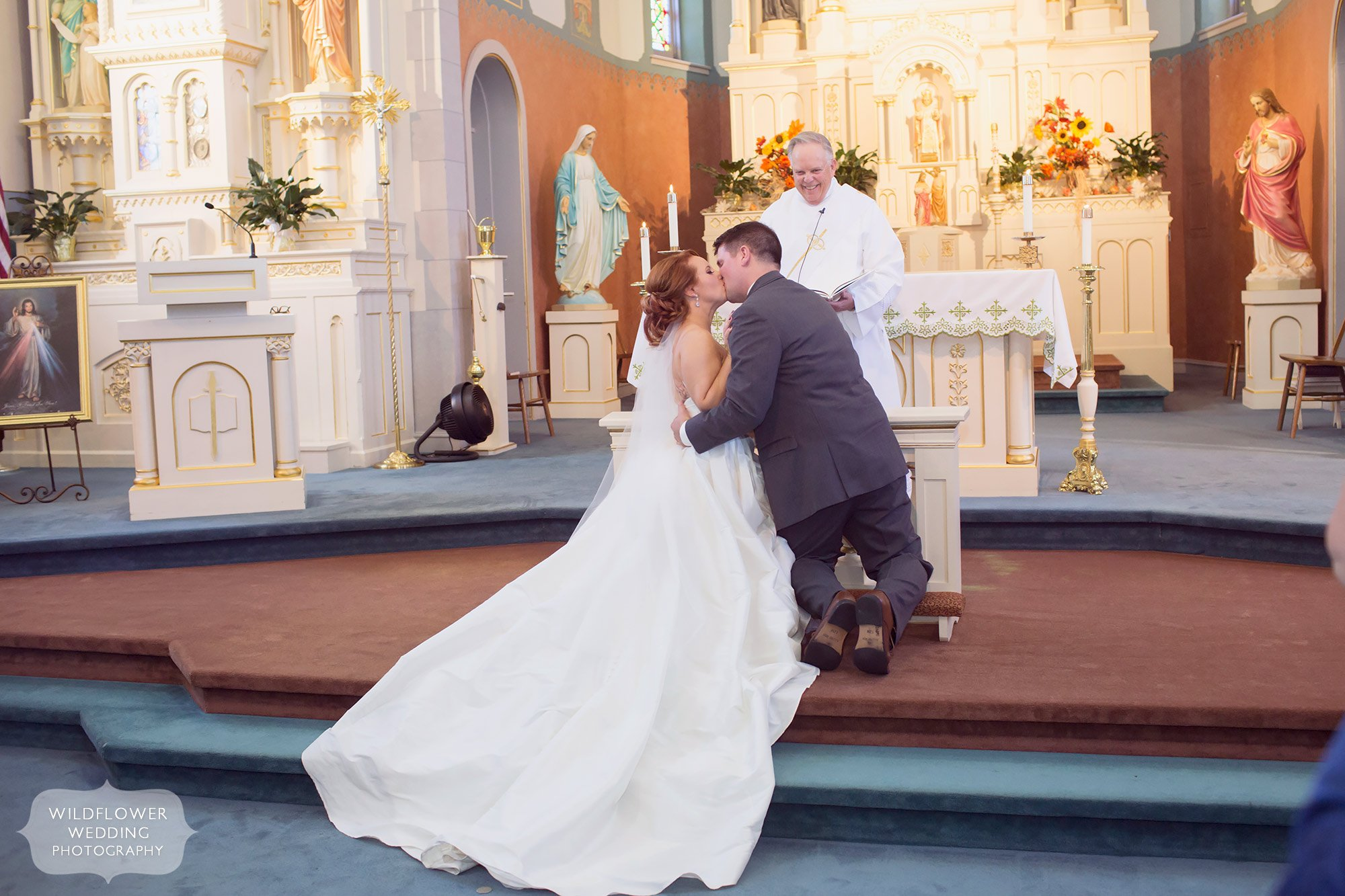 Bride and groom have a kneeling kiss at their church wedding in Jeff City.