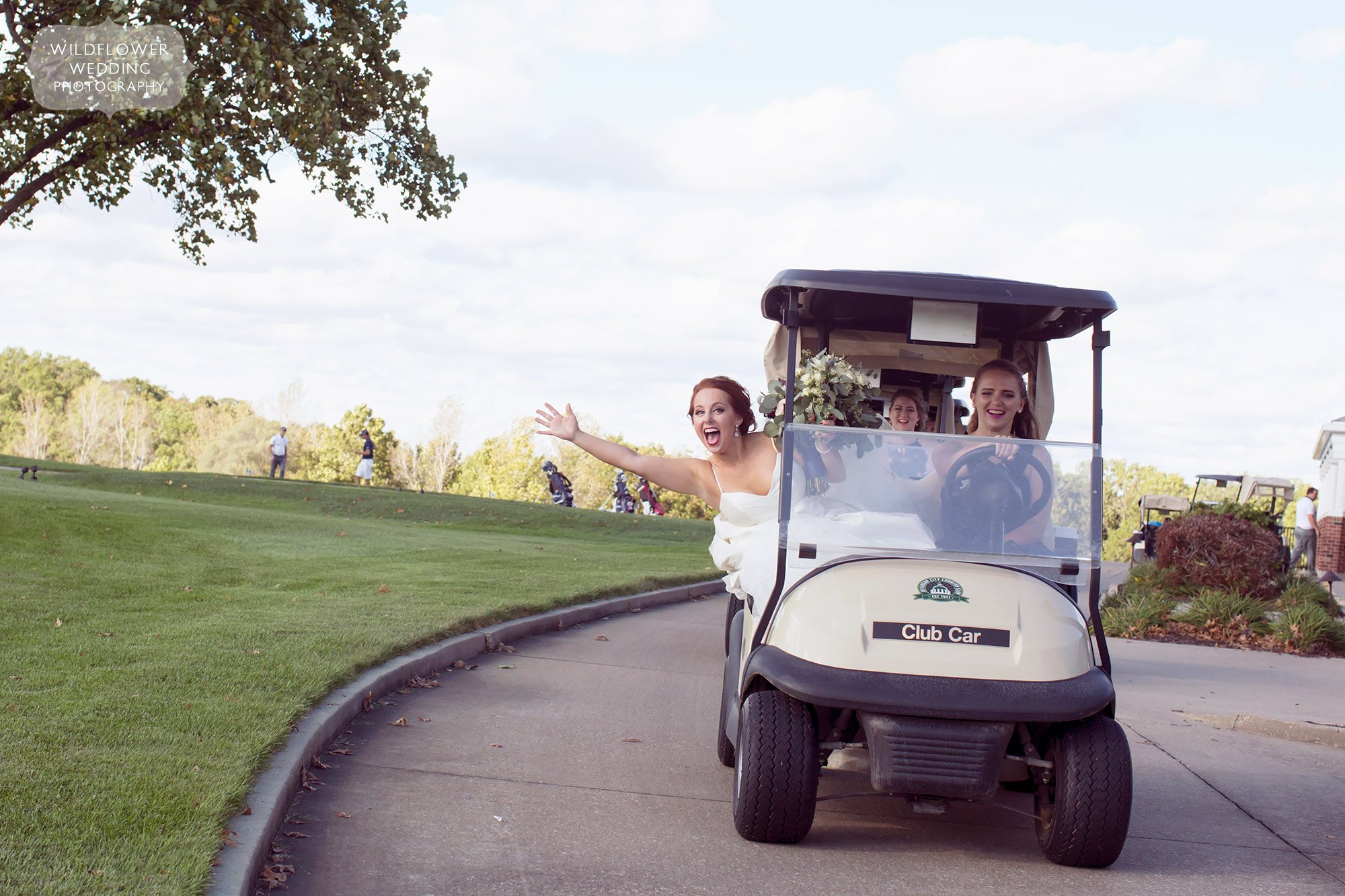 The bride smiling while riding in a golf cart at the Jefferson City Country Club.