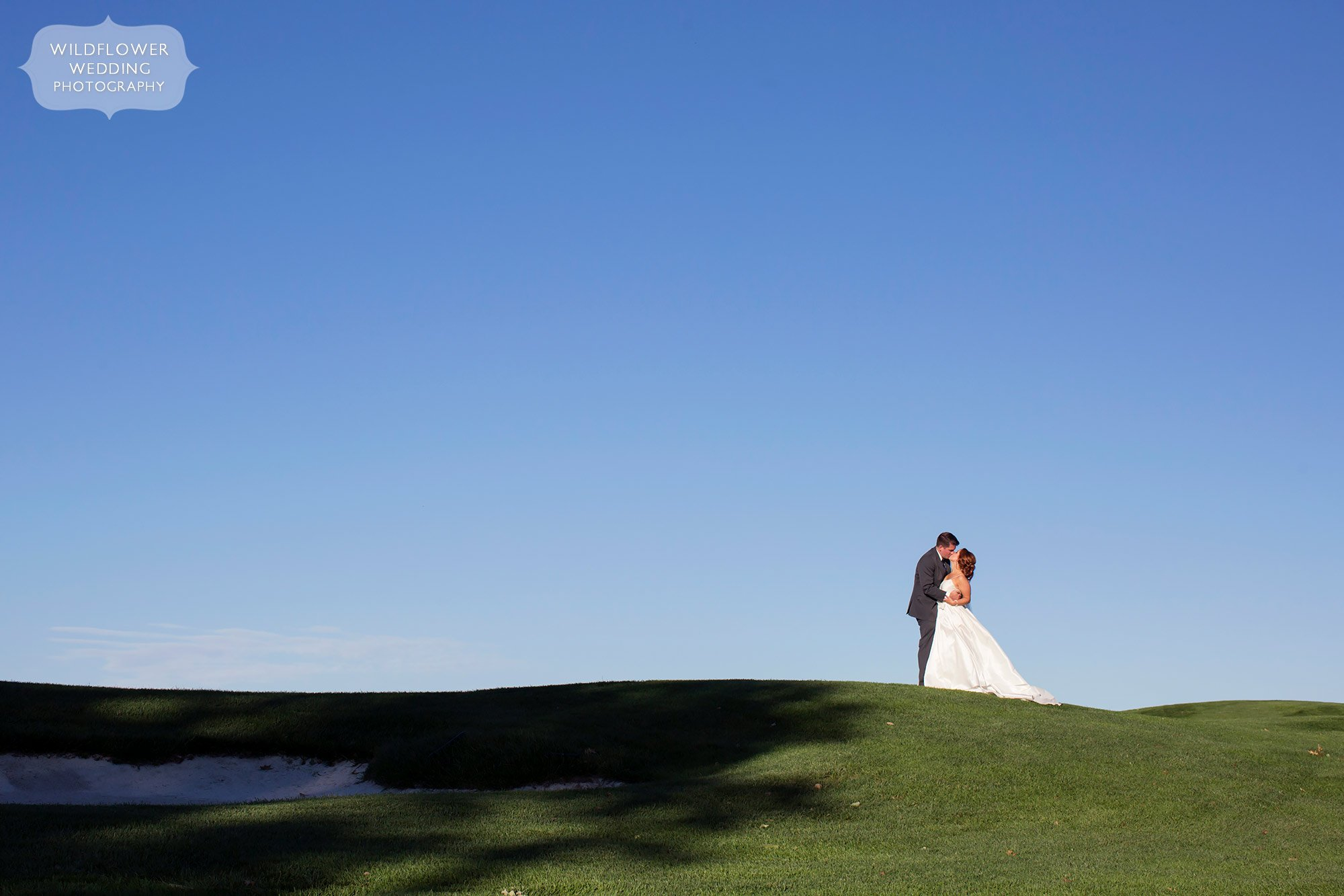 The bride and groom stand on a green hill against a blue sky at this Jefferson City Country Club wedding in MO.