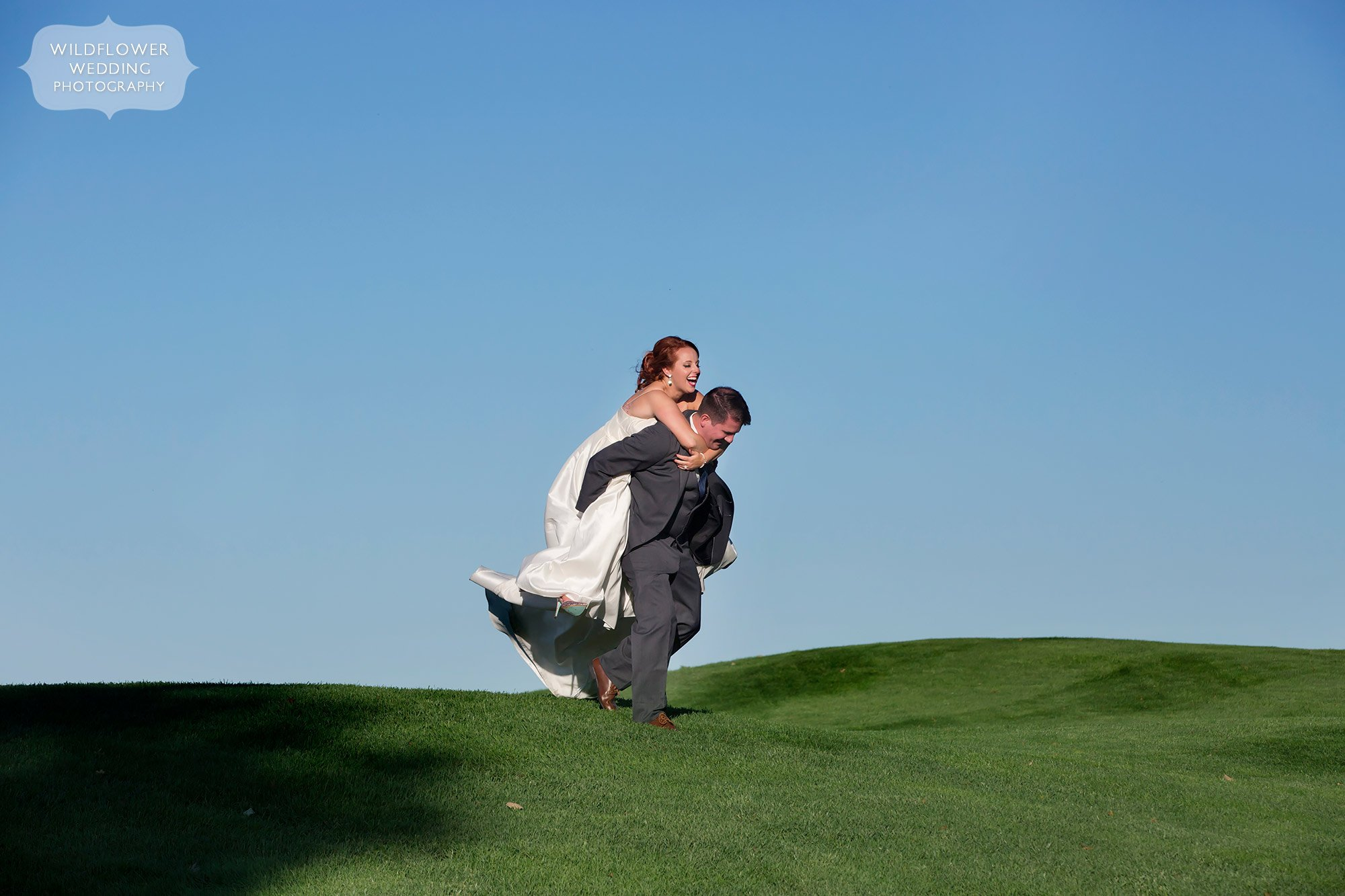 The groom gives the bride a piggyback ride at the Jeff City Country Club.