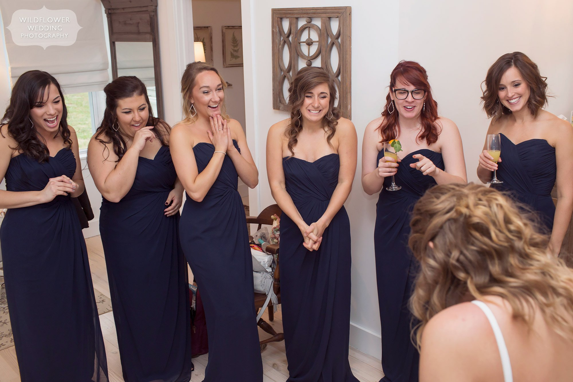The bridesmaids reaction to the bride wearing her wedding dress in the bridal cottage at Blue Bell Farm.