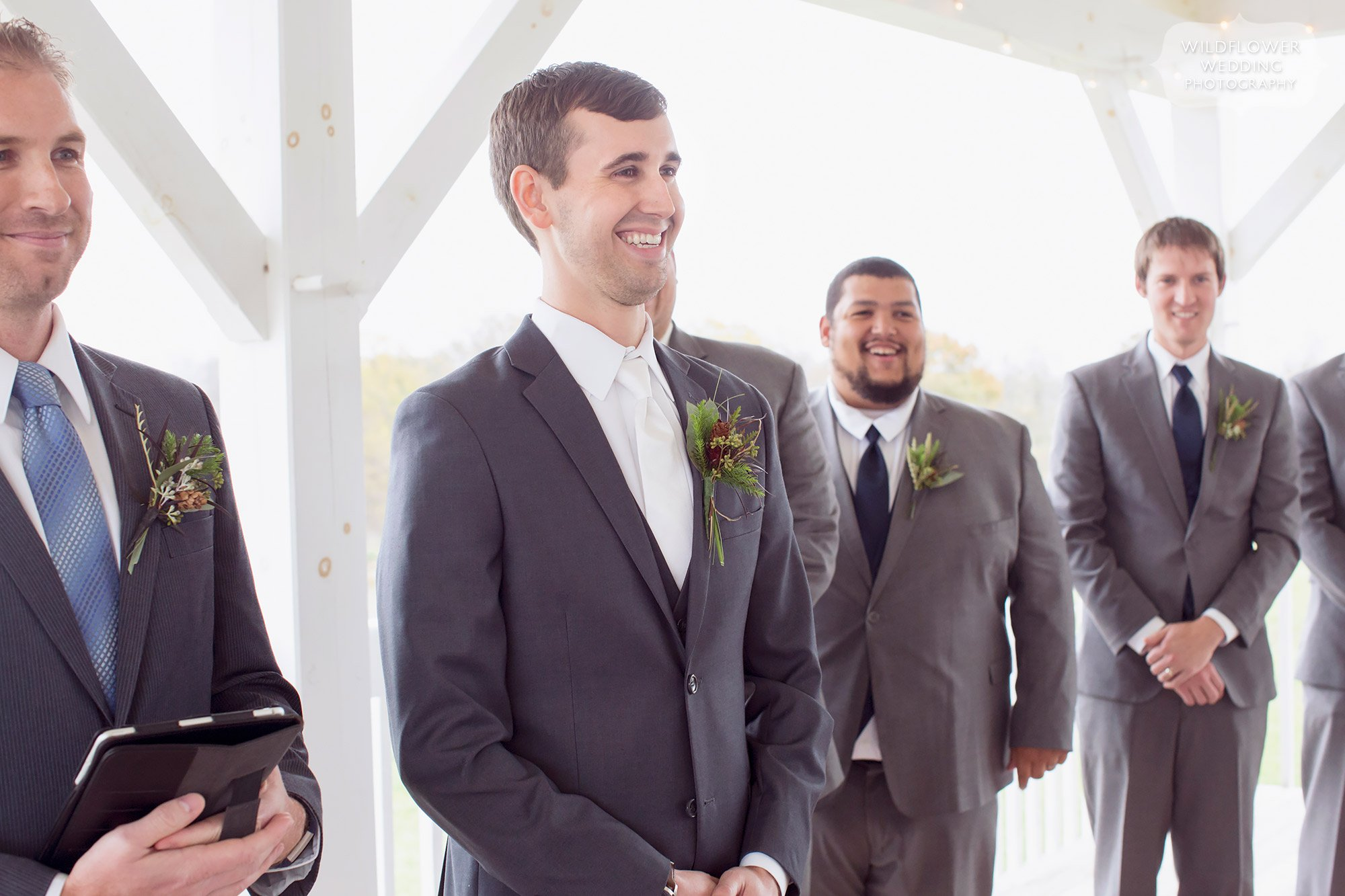 The groom watches the bride enter the outdoor deck ceremony at this barn wedding in MO.