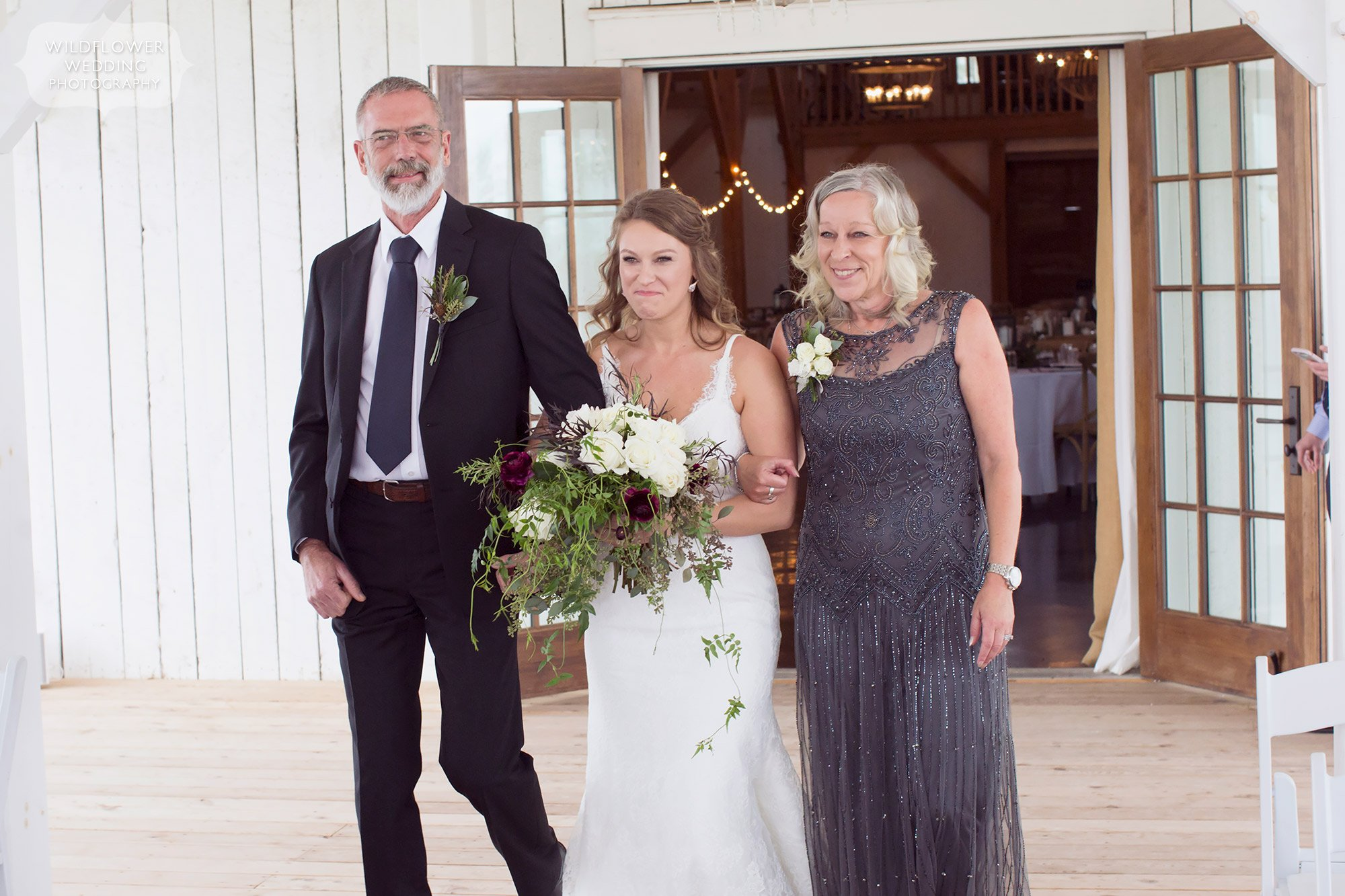 The bride walks into the ceremony with her parents at this Blue Bell Farm wedding in November.