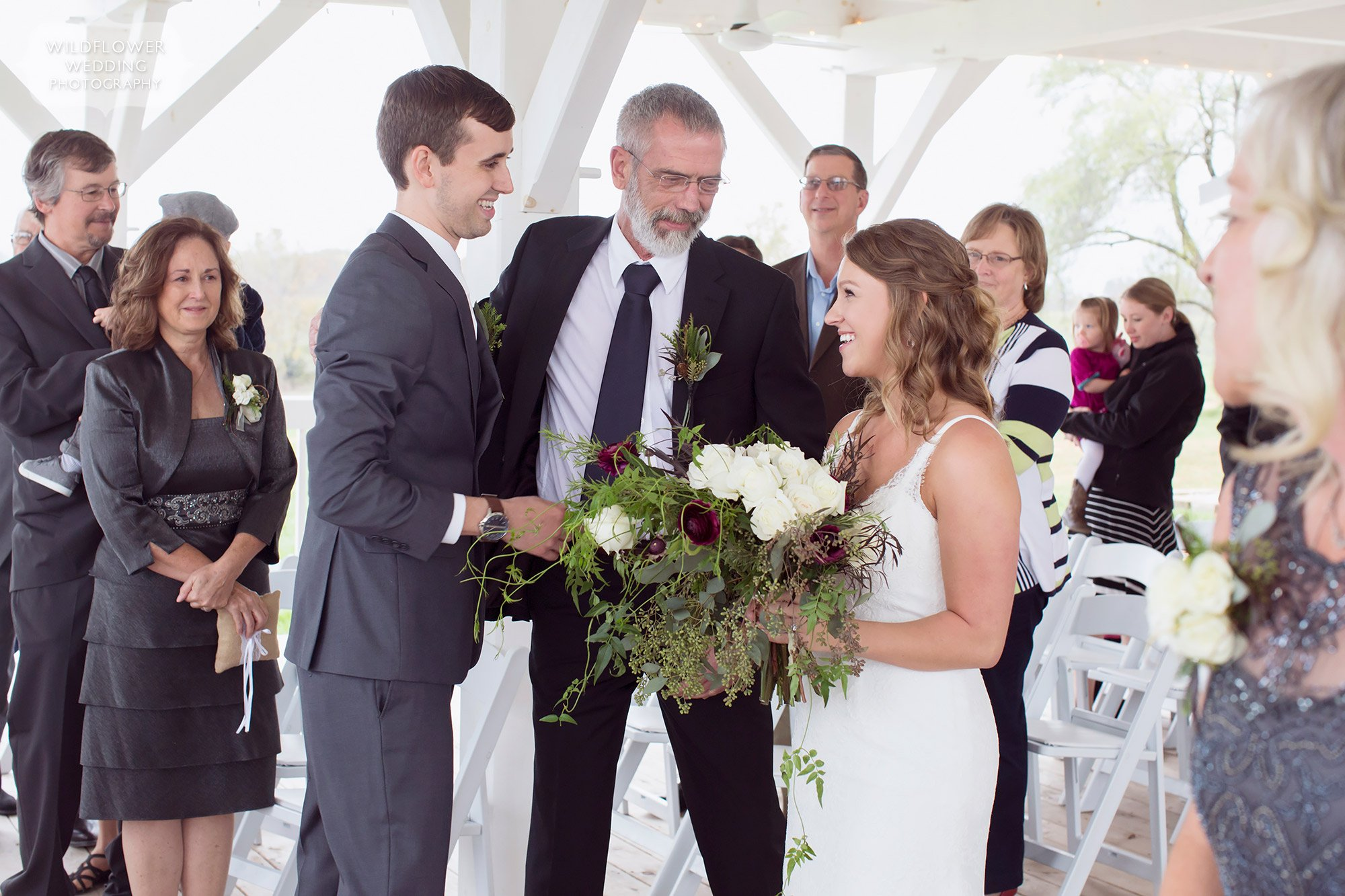The father gives bride away at outdoor ceremony on deck at Blue Bell Farm.