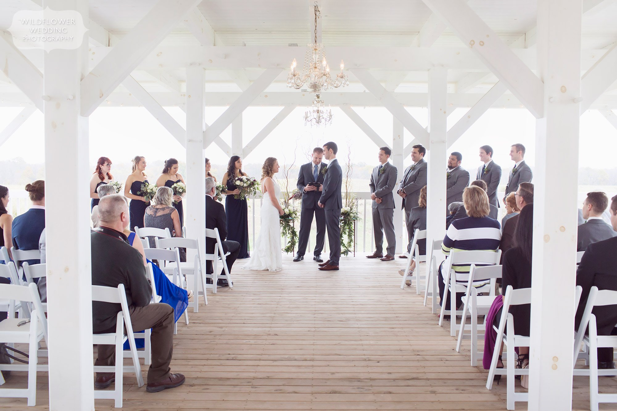 View of an outdoor ceremony on the covered deck at the Blue Bell Farm in Fayette, MO.