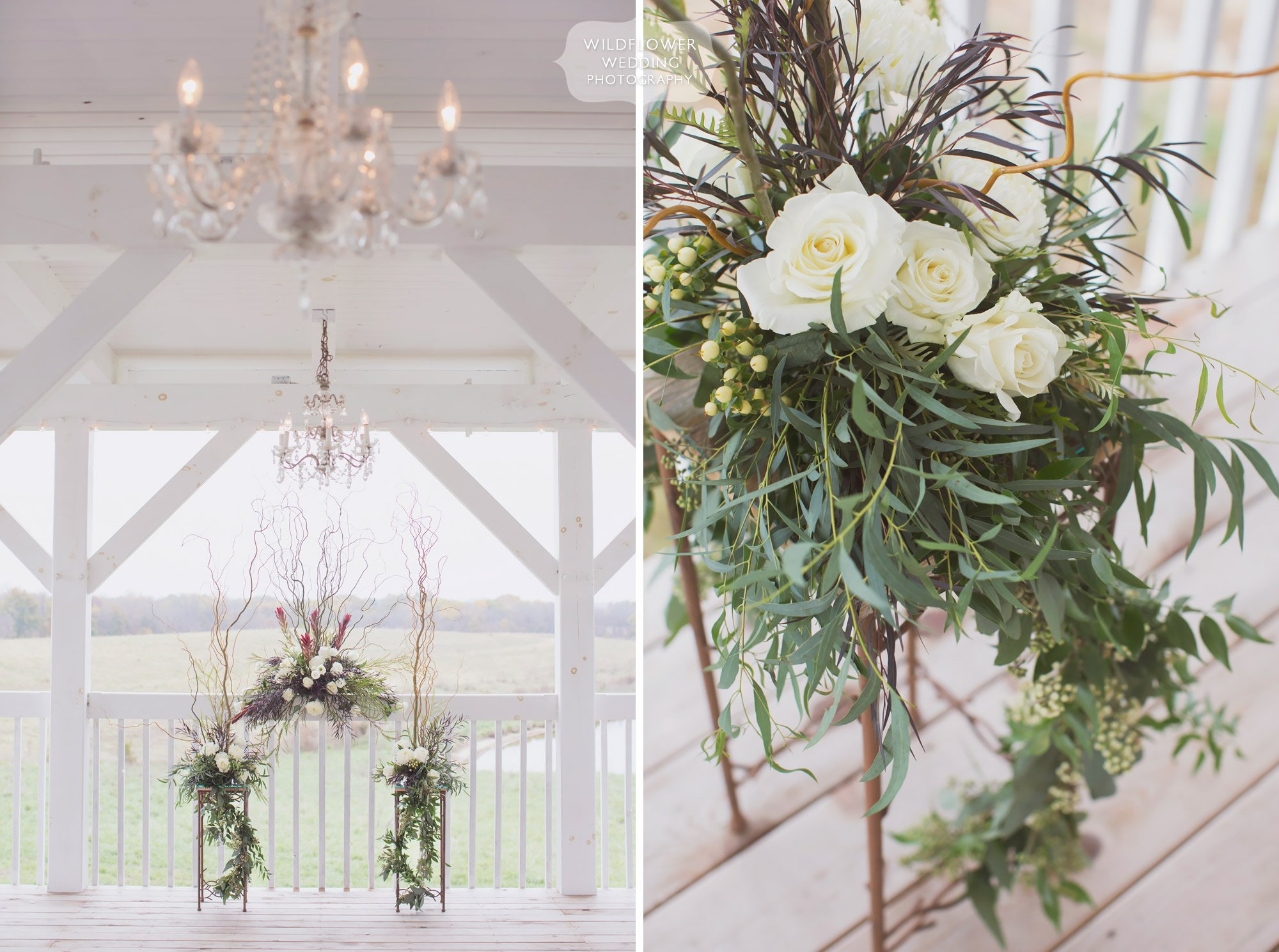 View of the white outdoor deck ceremony space at the Blue Bell Farm with a trailing floral arbor.