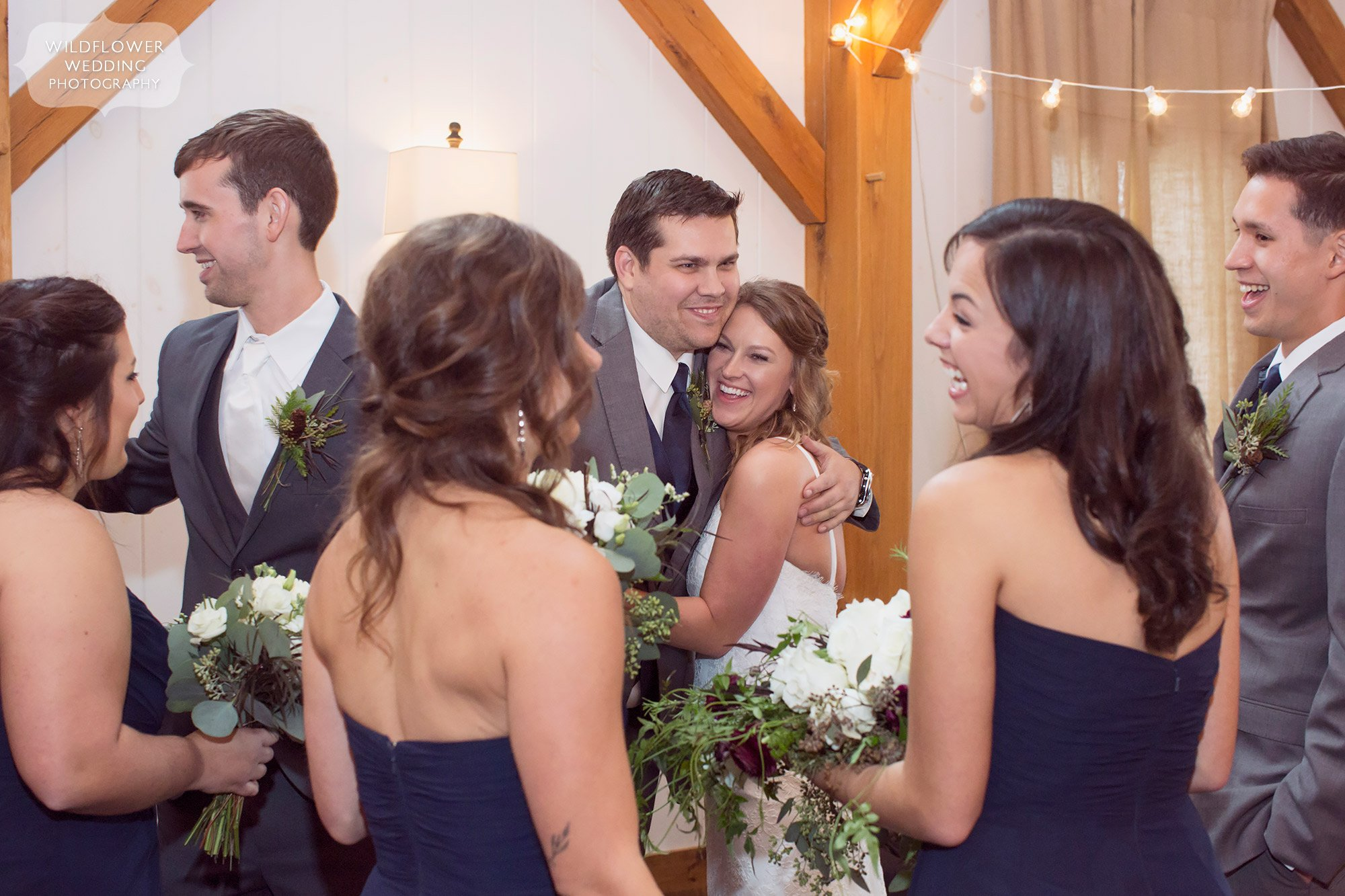 The wedding party congratulates the bride and groom at this rustic timber frame wedding venue in Fayette.