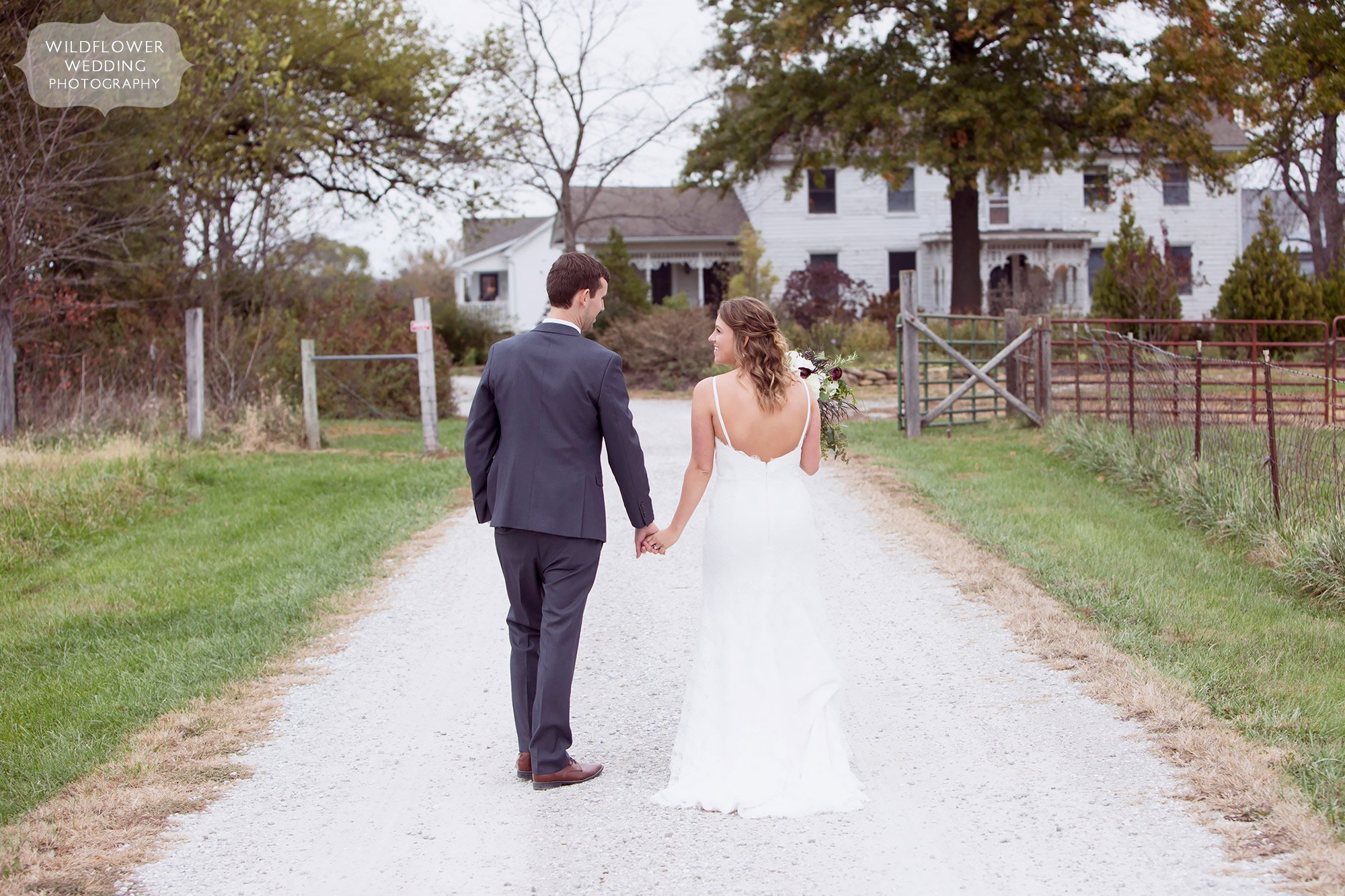 The bride and groom hold hands while walking down the gravel road to the Blue Bell Farm wedding venue in mid-MO.
