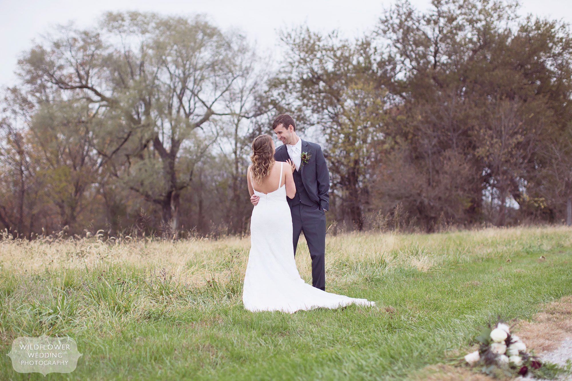 The bride and groom embrace in a grassy field at the Blue Bell Farm in Fayette, MO.