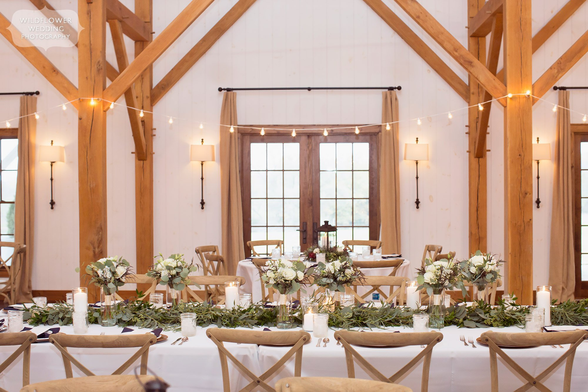 The bright and airy head table set up at the Blue Bell Farm with wooden cafe chairs in Fayette.