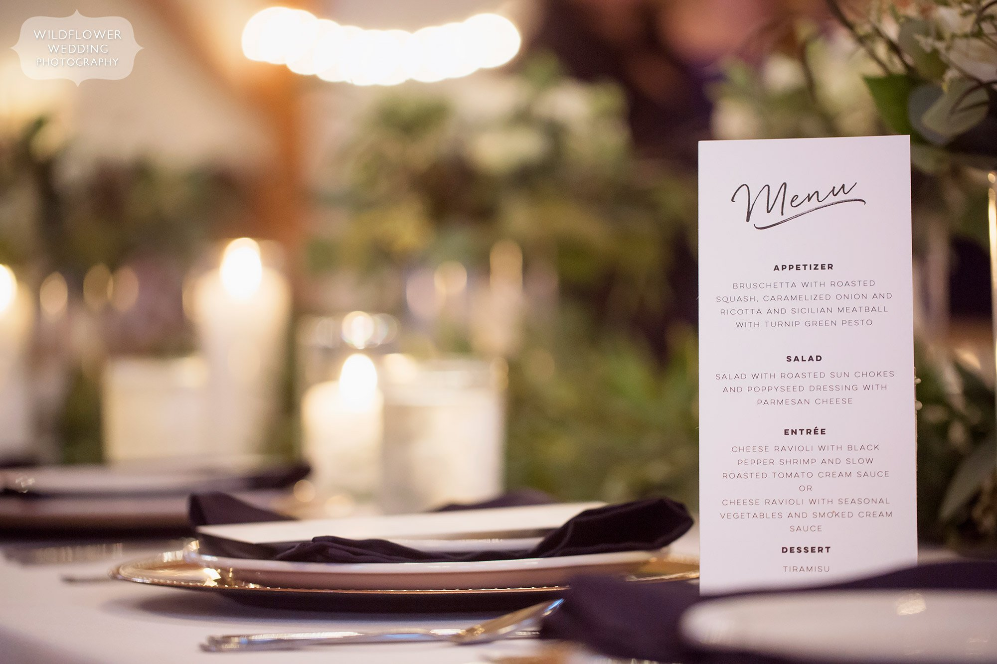 Romantic flowers and candles on the tables at the Blue Bell Farm wedding venue with simple paper menu.