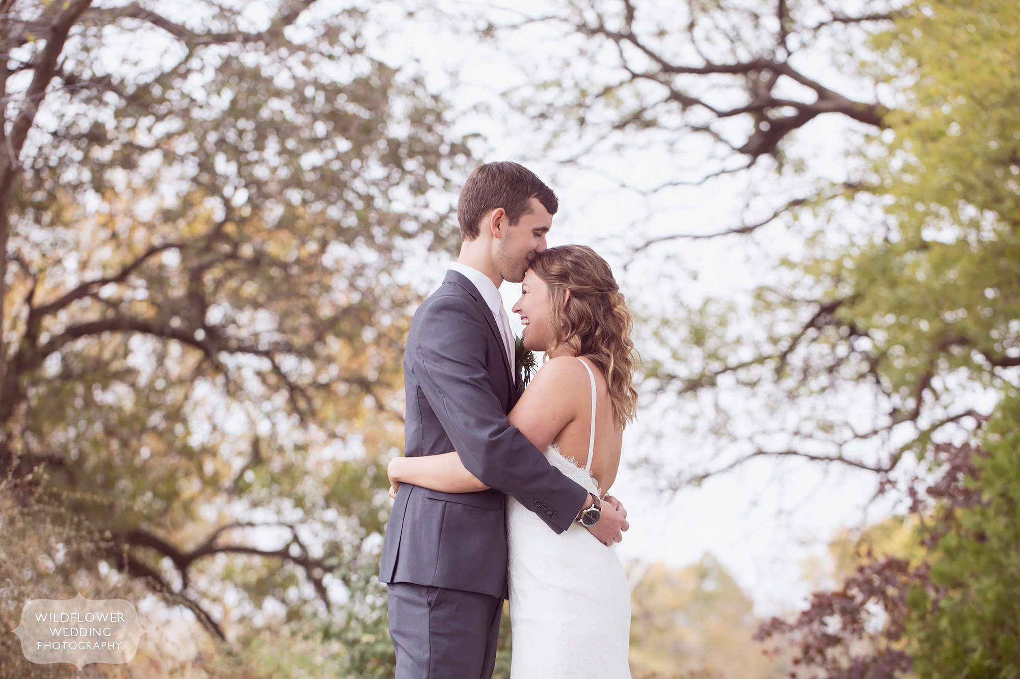 Unique wedding photography with artistic composition of bride and groom under trees at the Blue Bell Farm.