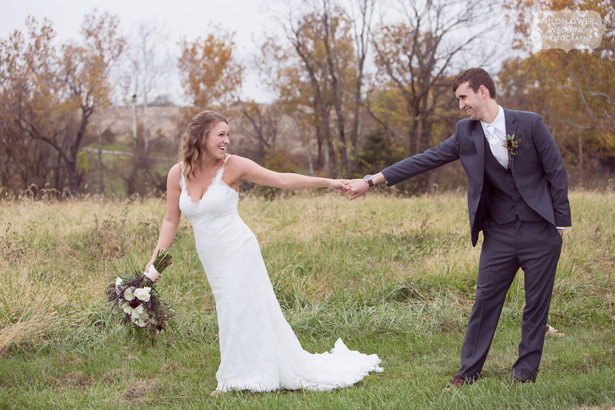 The bride pulls her groom along the edge of a tall grass field at their farm wedding in Fayette.