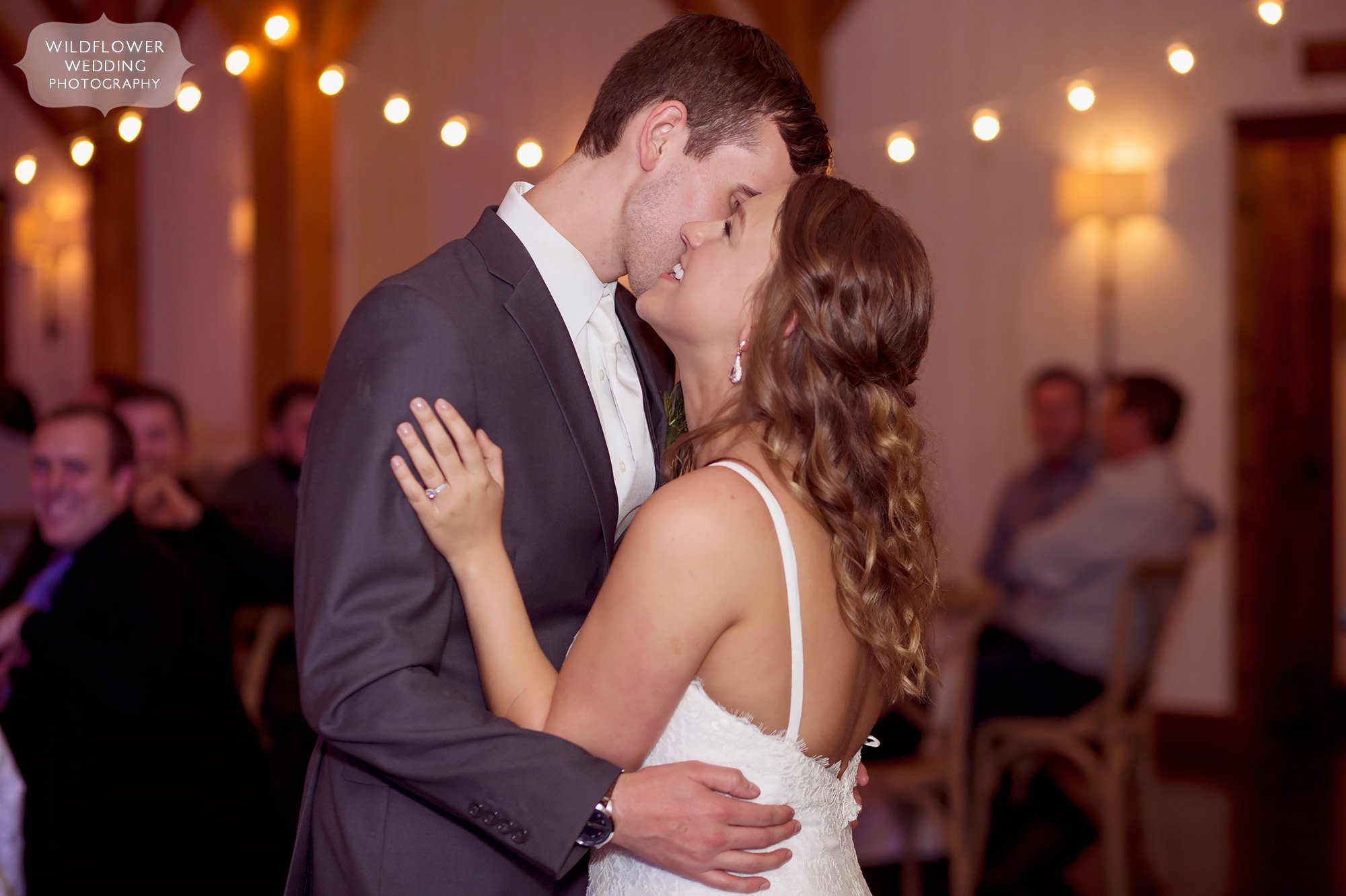 The bride and groom kiss on the dance floor with twinkle lights blurry in background behind them.