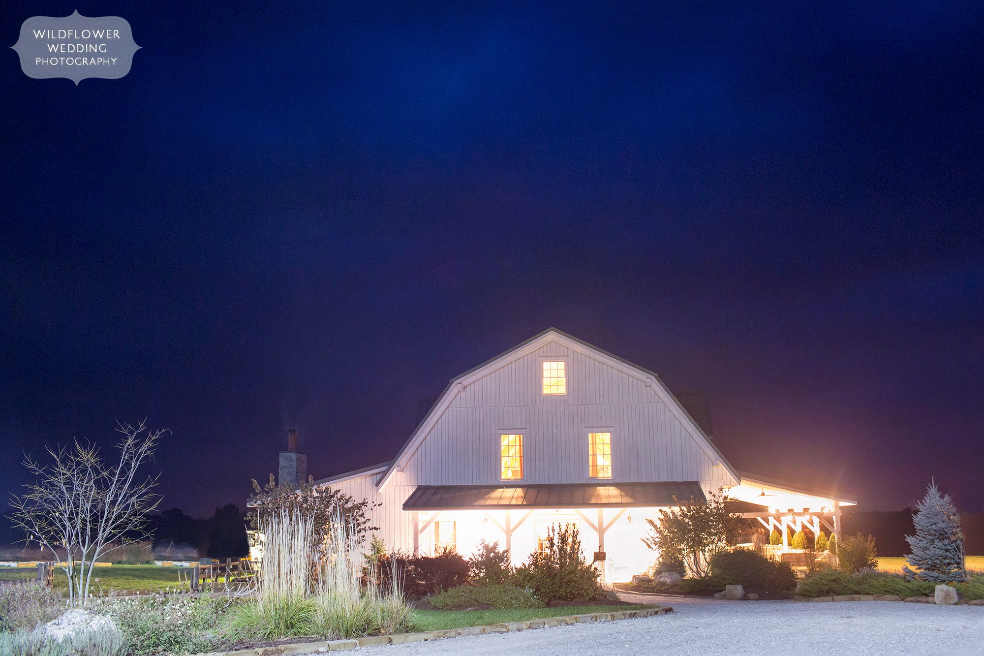 The white barn at Blue Bell Farm glows in the twilight for this outdoor November wedding near Columbia, MO.