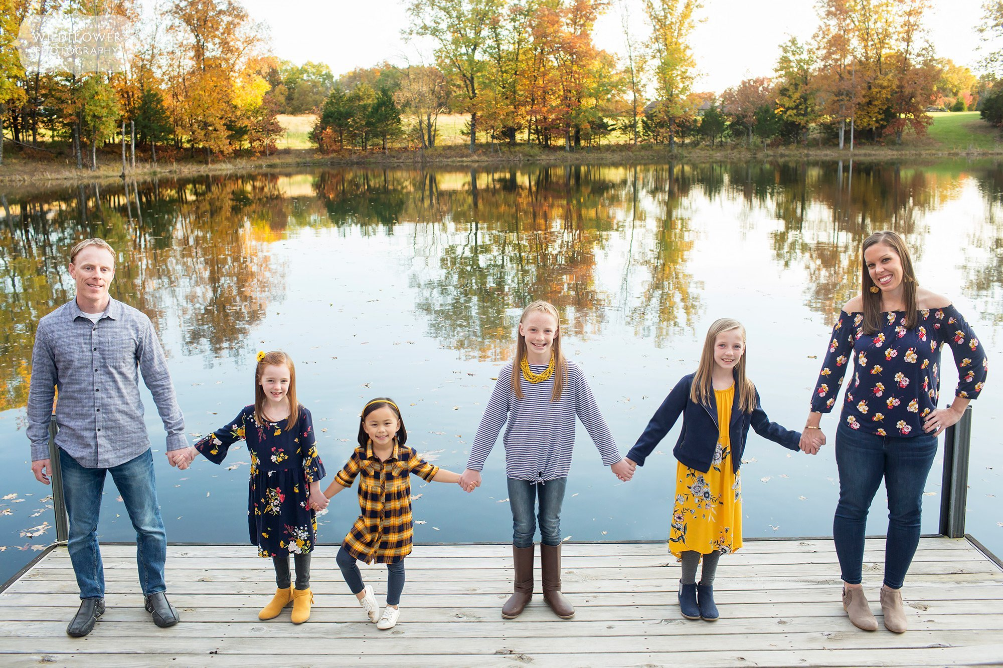 These fall family pictures in Columbia, MO have family line up on a dock with lake behind them.