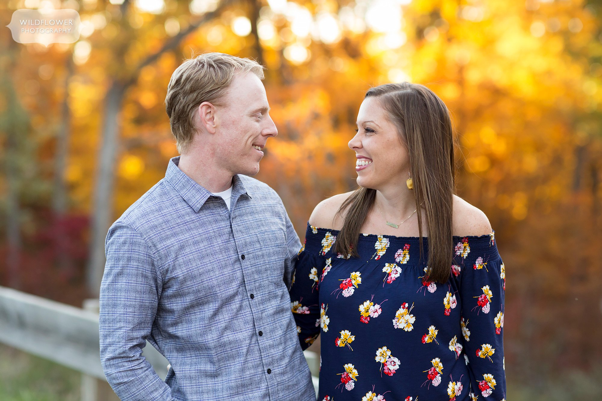 Parents smile at each other during this October family photography session in Columbia, MO.