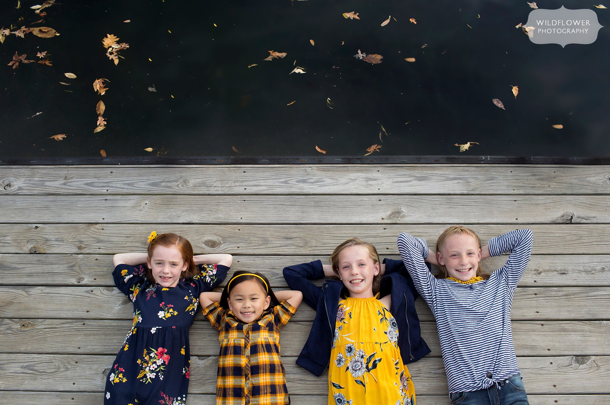 Kids lay on a dock in Columbia, MO during this fall family photo session.