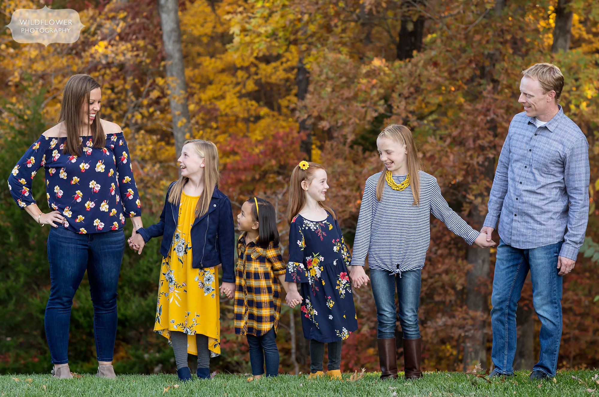 Family holds hands in front of colorful October foliage at their home in Columbia, MO.