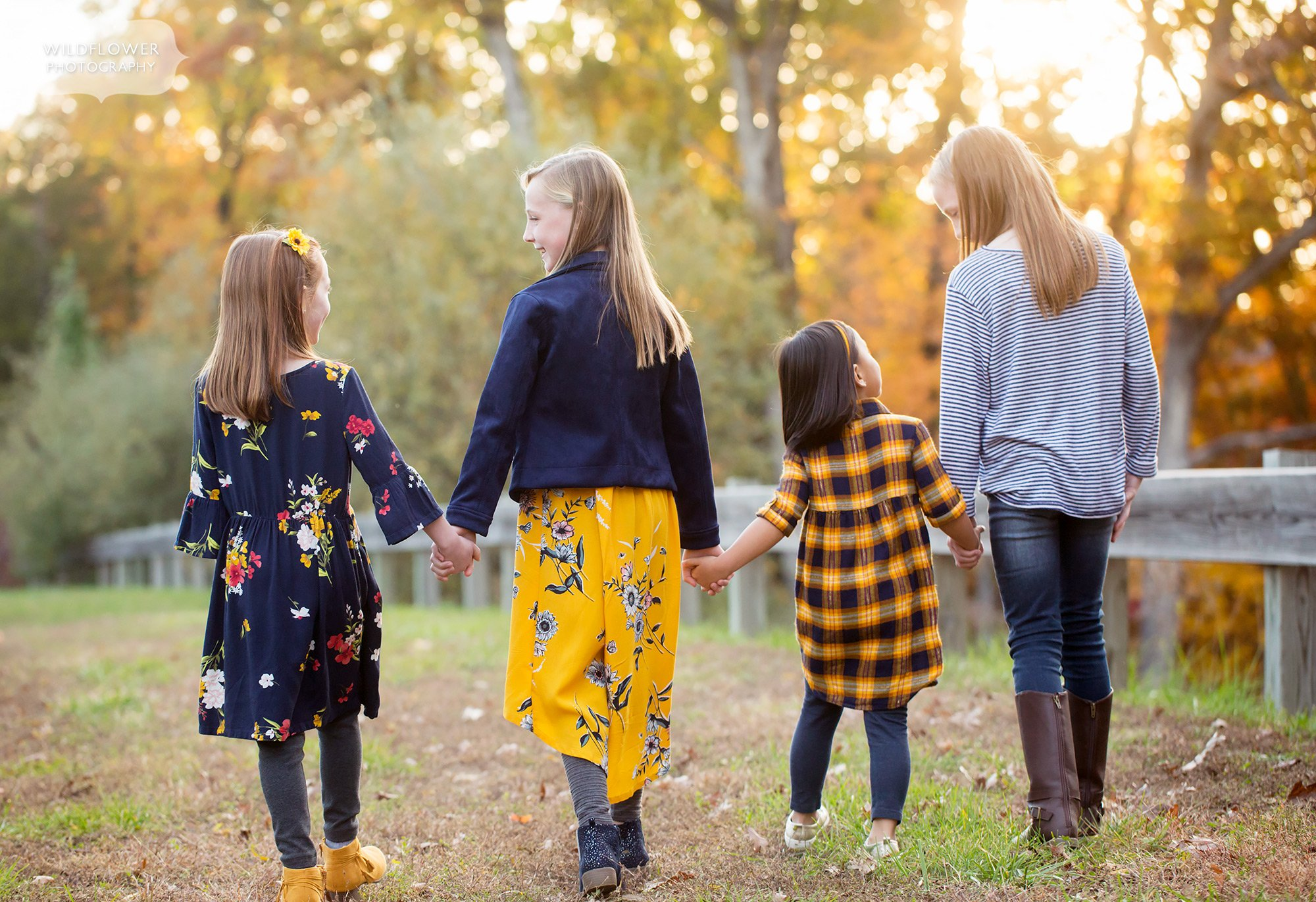 Sweet family photo at sunset in October of sisters holding hands and walking down path.